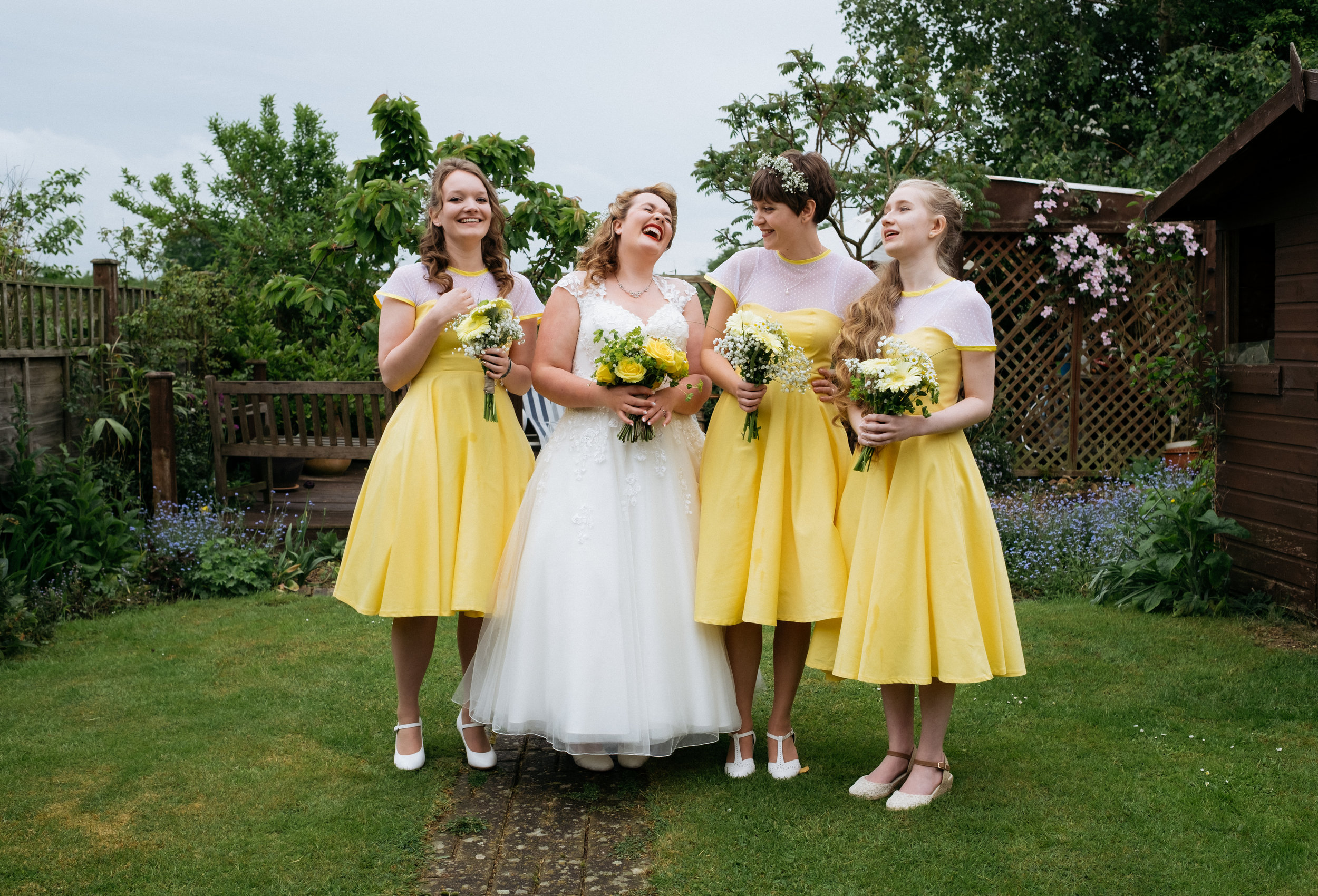 Bride and bridesmaids laughing in a back garden