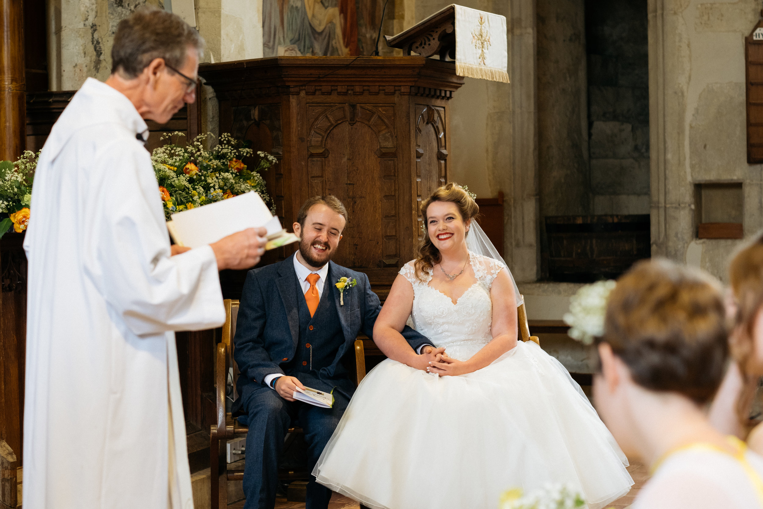 Bride and groom laughing in church
