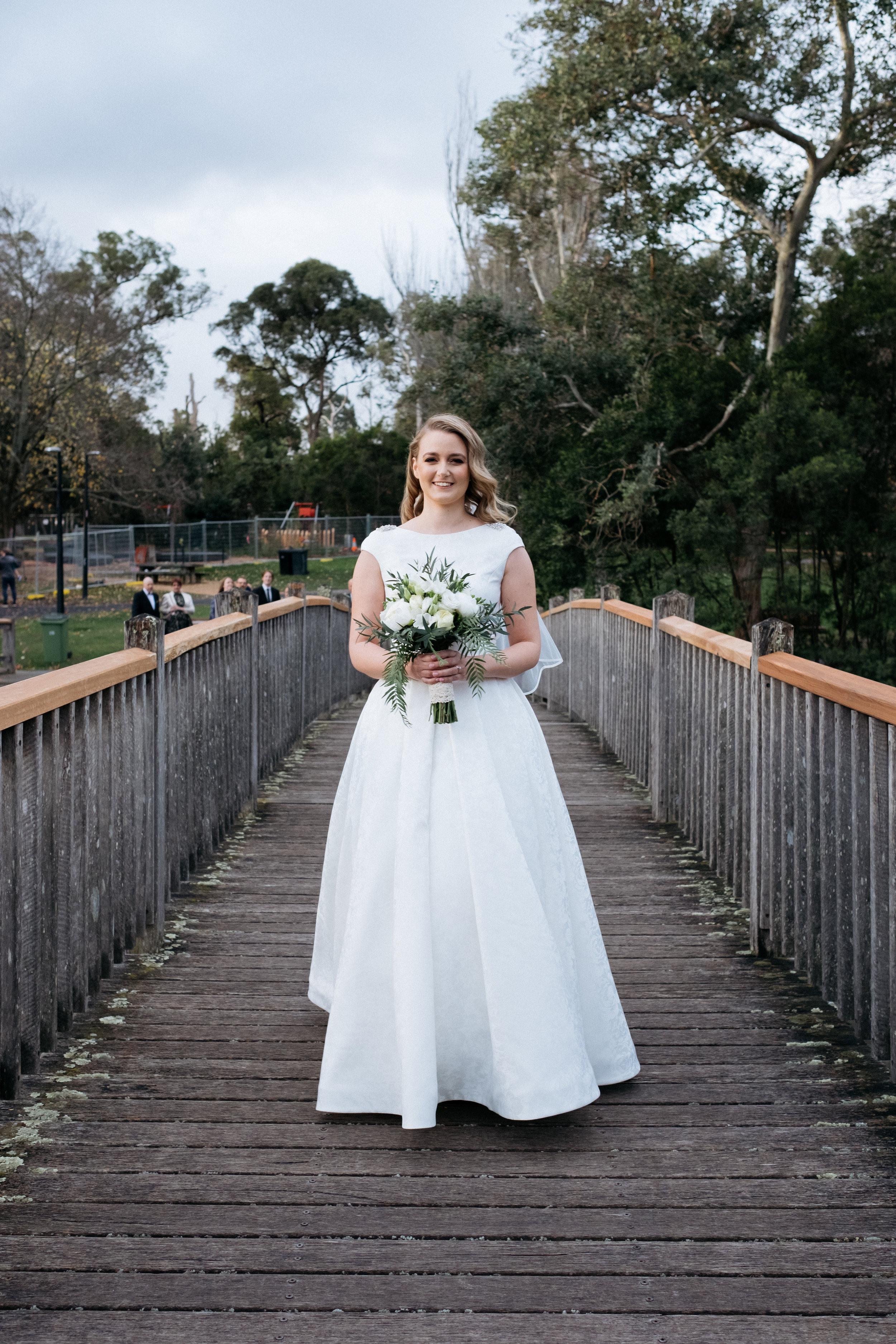 Bride walking across bridge for first look