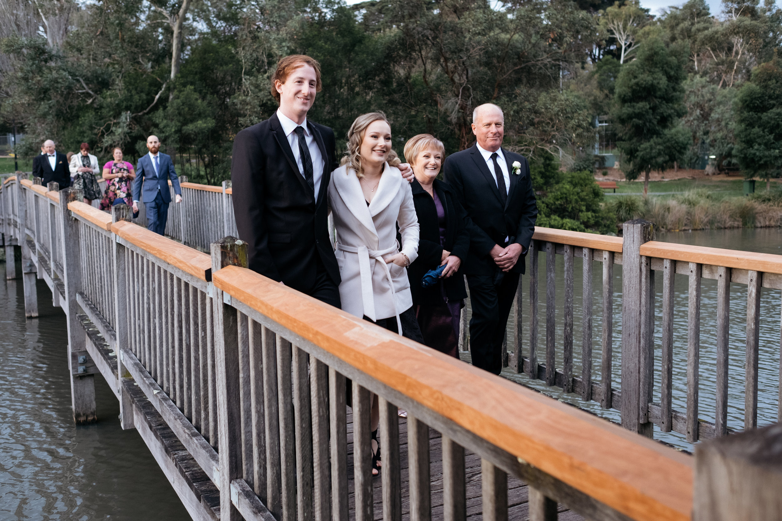 Family walking across bridge see bride and groom for the first time