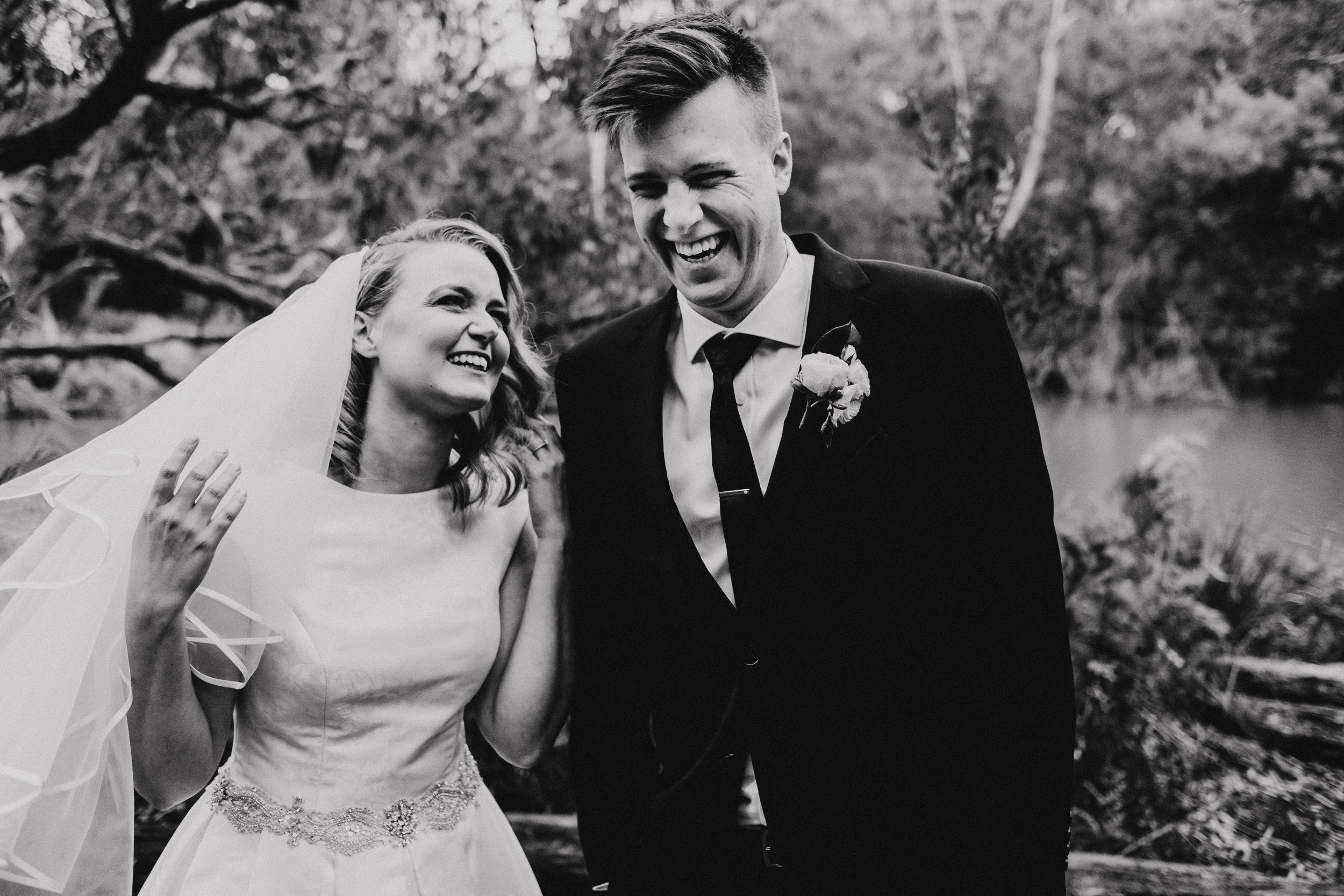 Bride and groom laughing in black and white