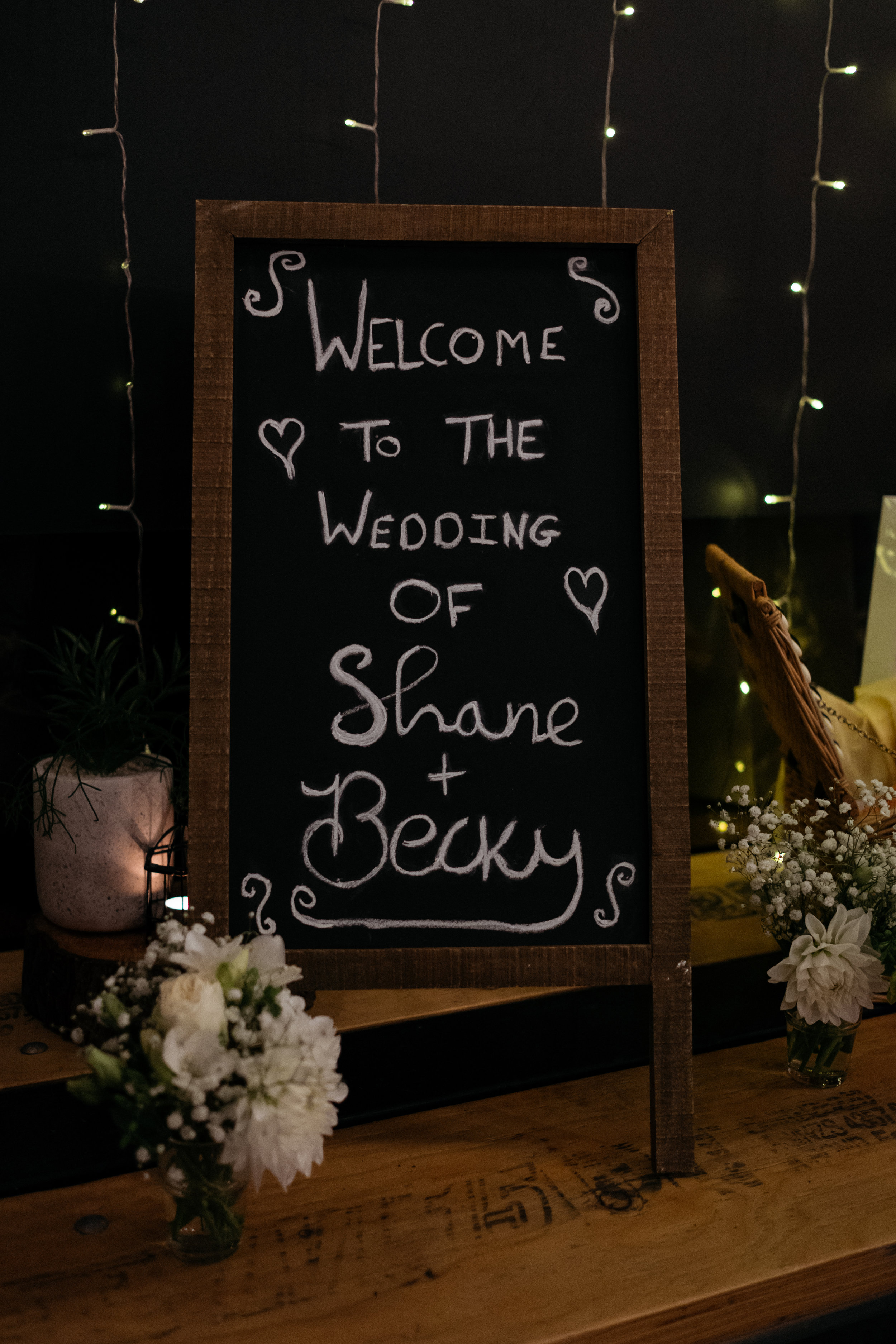 Handwritten wedding sign reading 'welcome to the wedding of Shane and Becky'