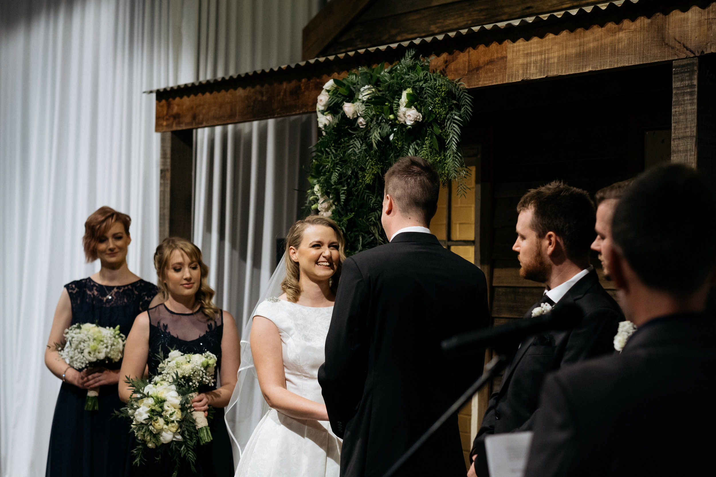 Bride smiling while groom reads his vows at The Budgie Smuggler, Ringwood, VIC