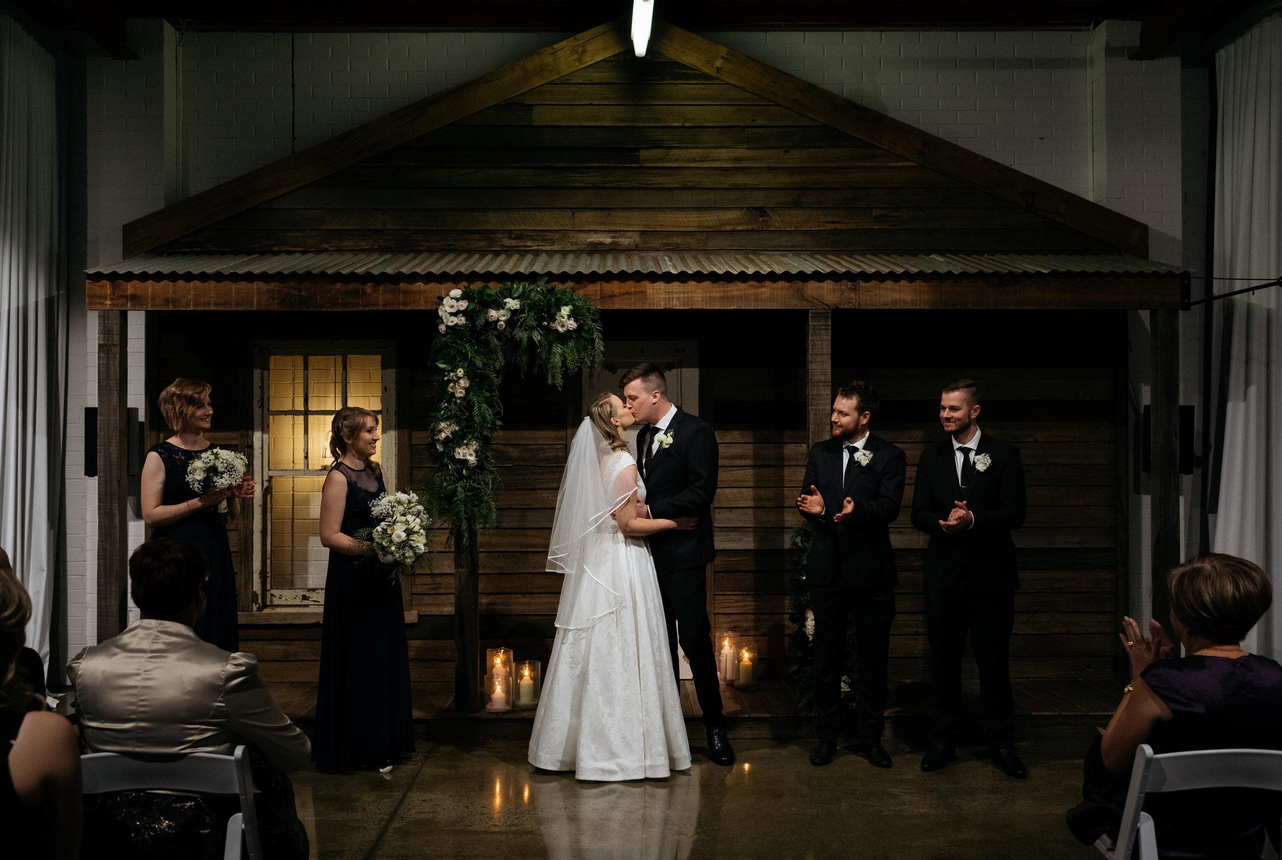 Bride and groom kiss at The Budgie Smuggler, Ringwood, VIC