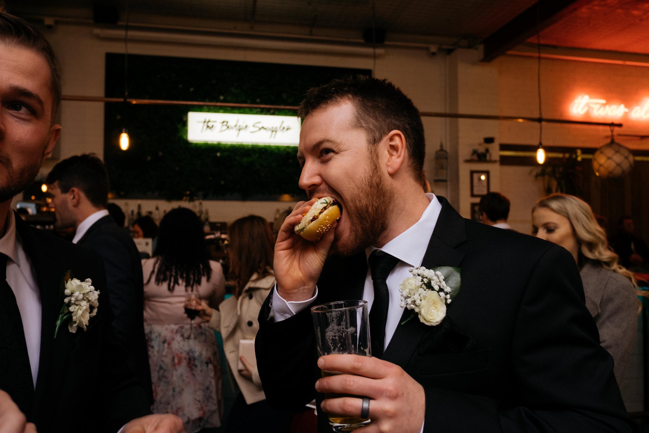 Groomsman eating a burger