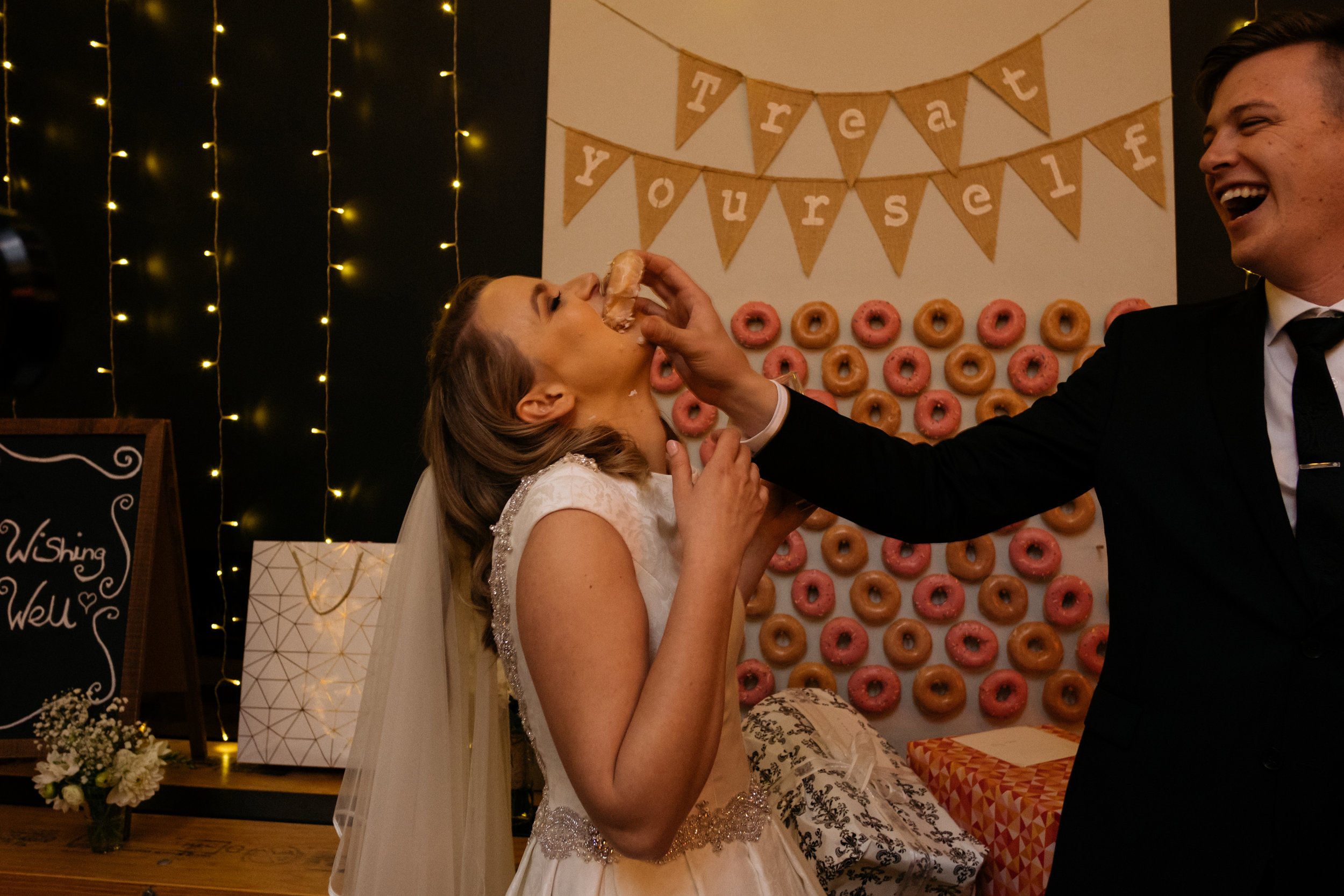 Groom shoving a donut in bride's face