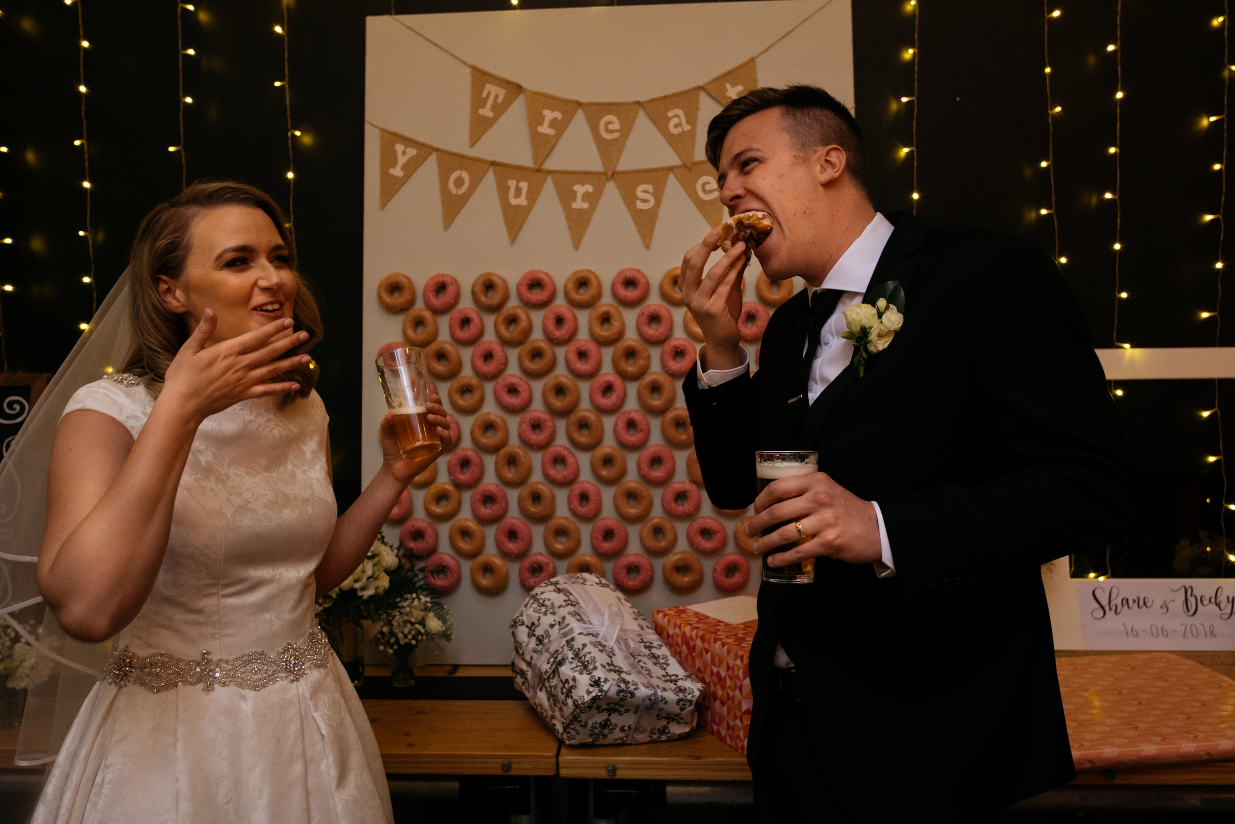 Bride and groom eating donuts after wedding ceremony