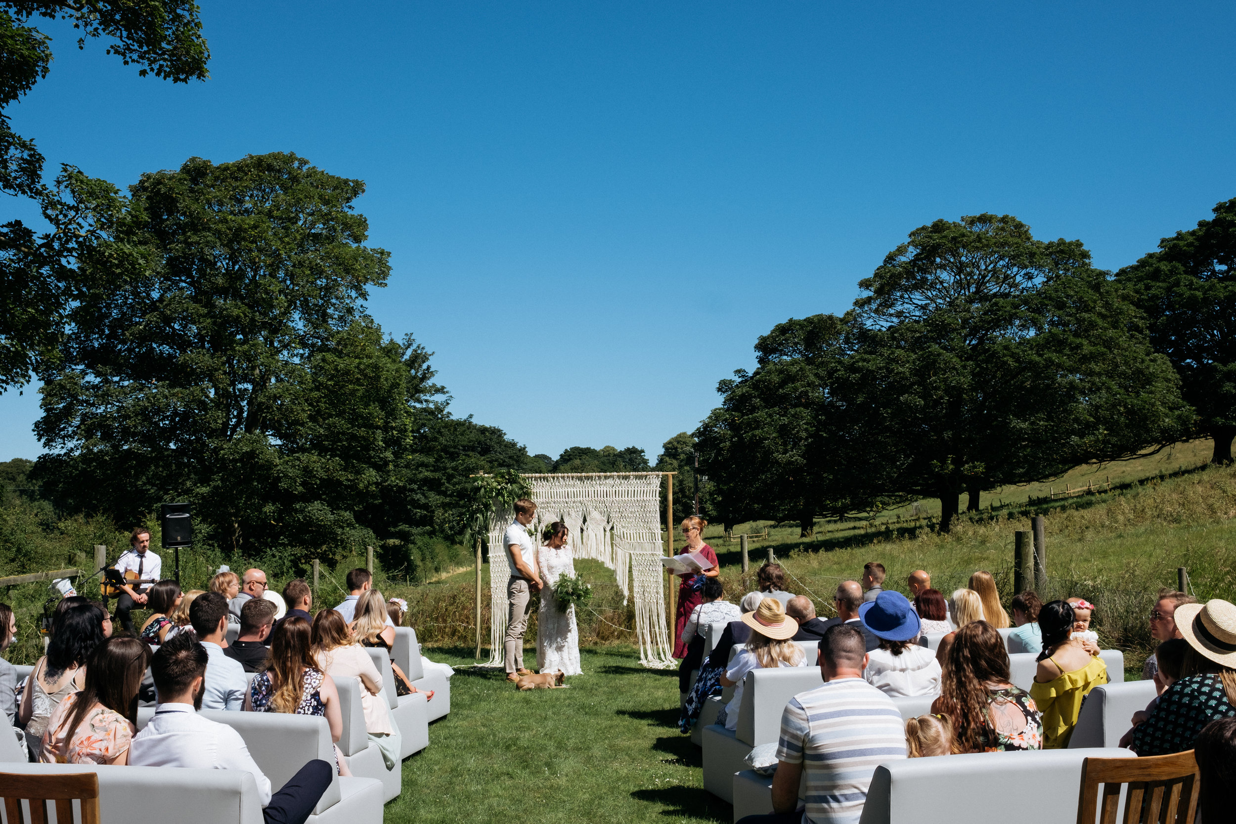 Outdoor wedding ceremony with macrame wedding arch