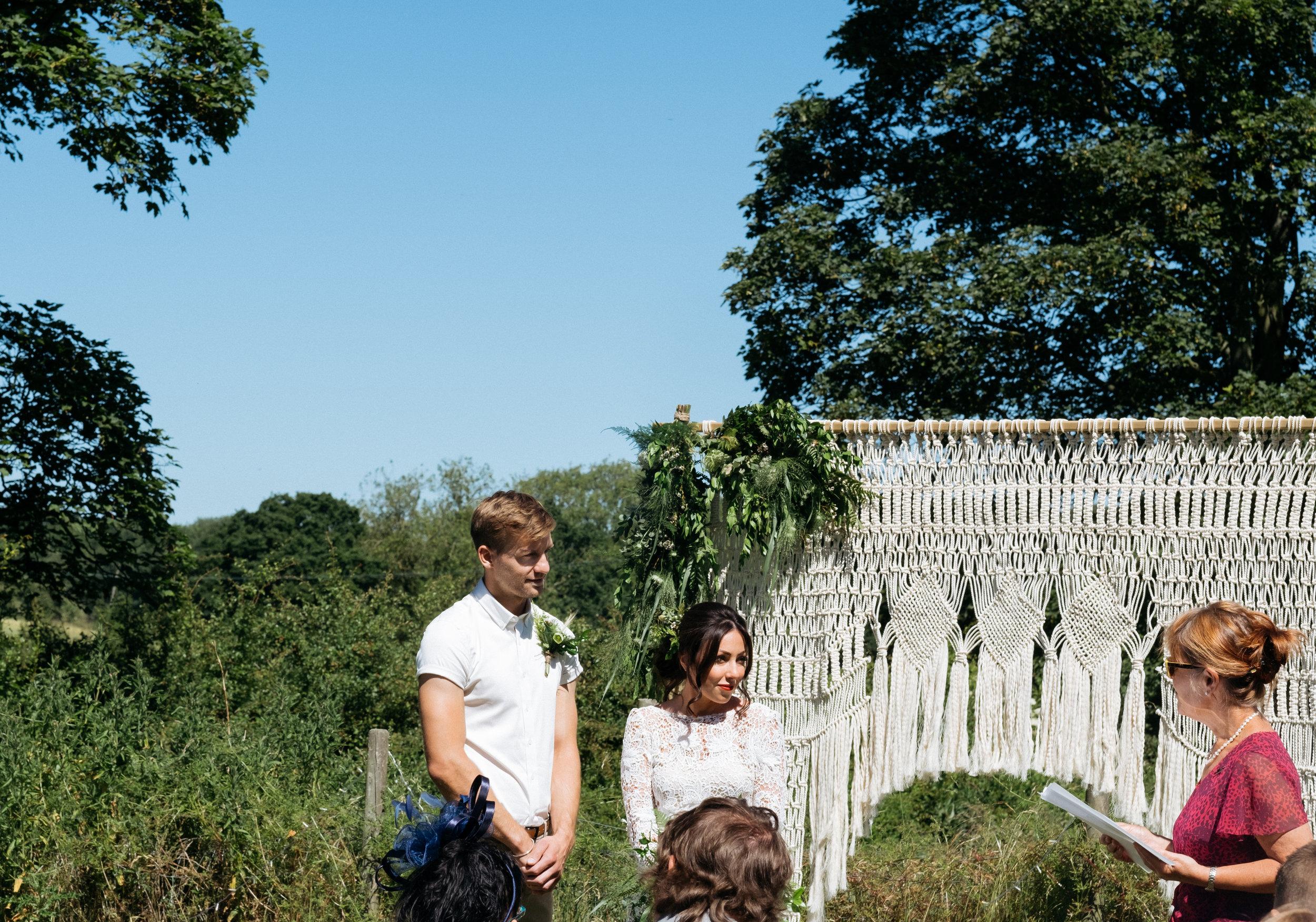 Outdoor wedding ceremony with macrame wedding arch