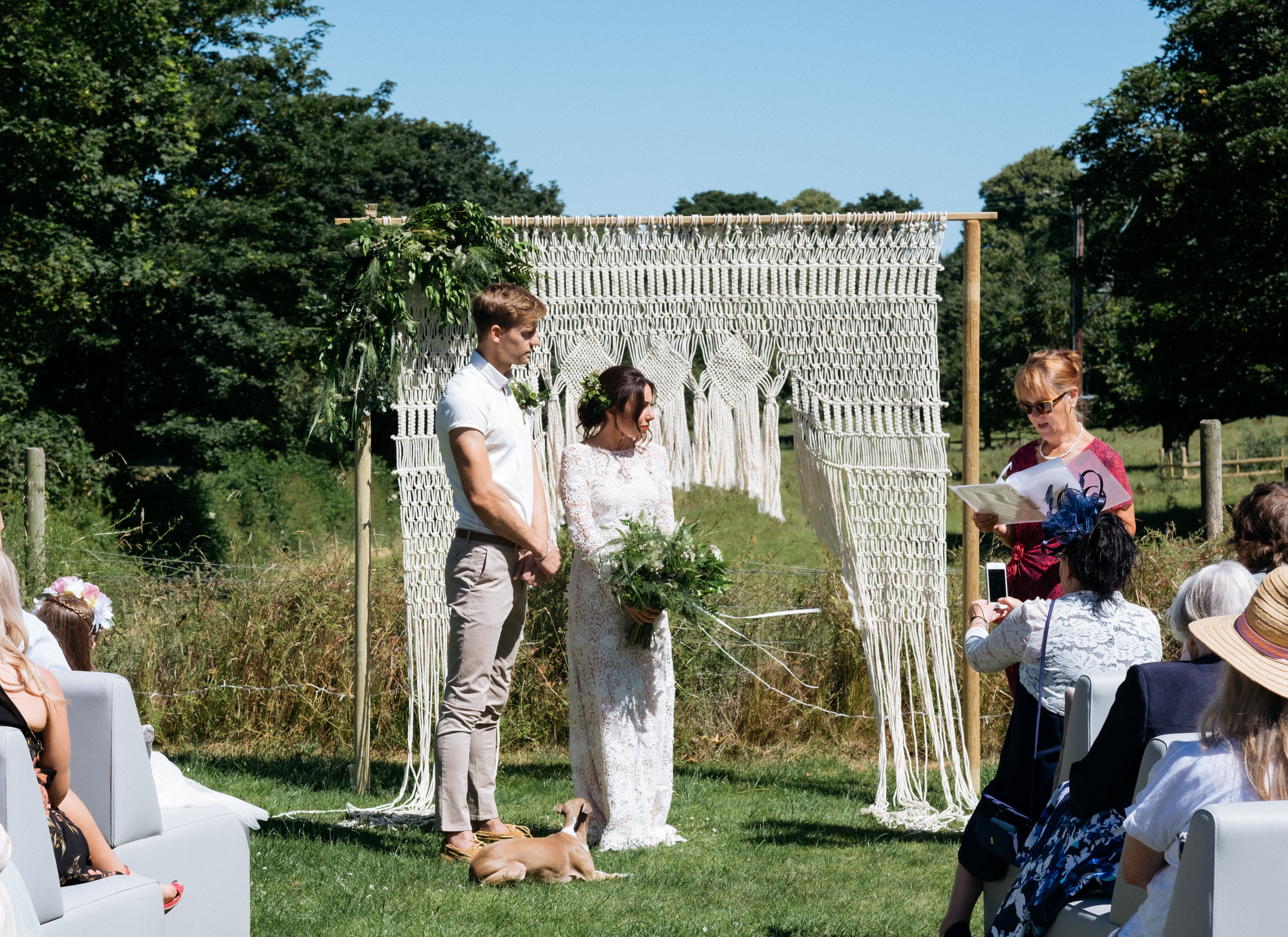 Bride and groom getting married in outdoor wedding ceremony with Italian greyhound and macrame wedding arch
