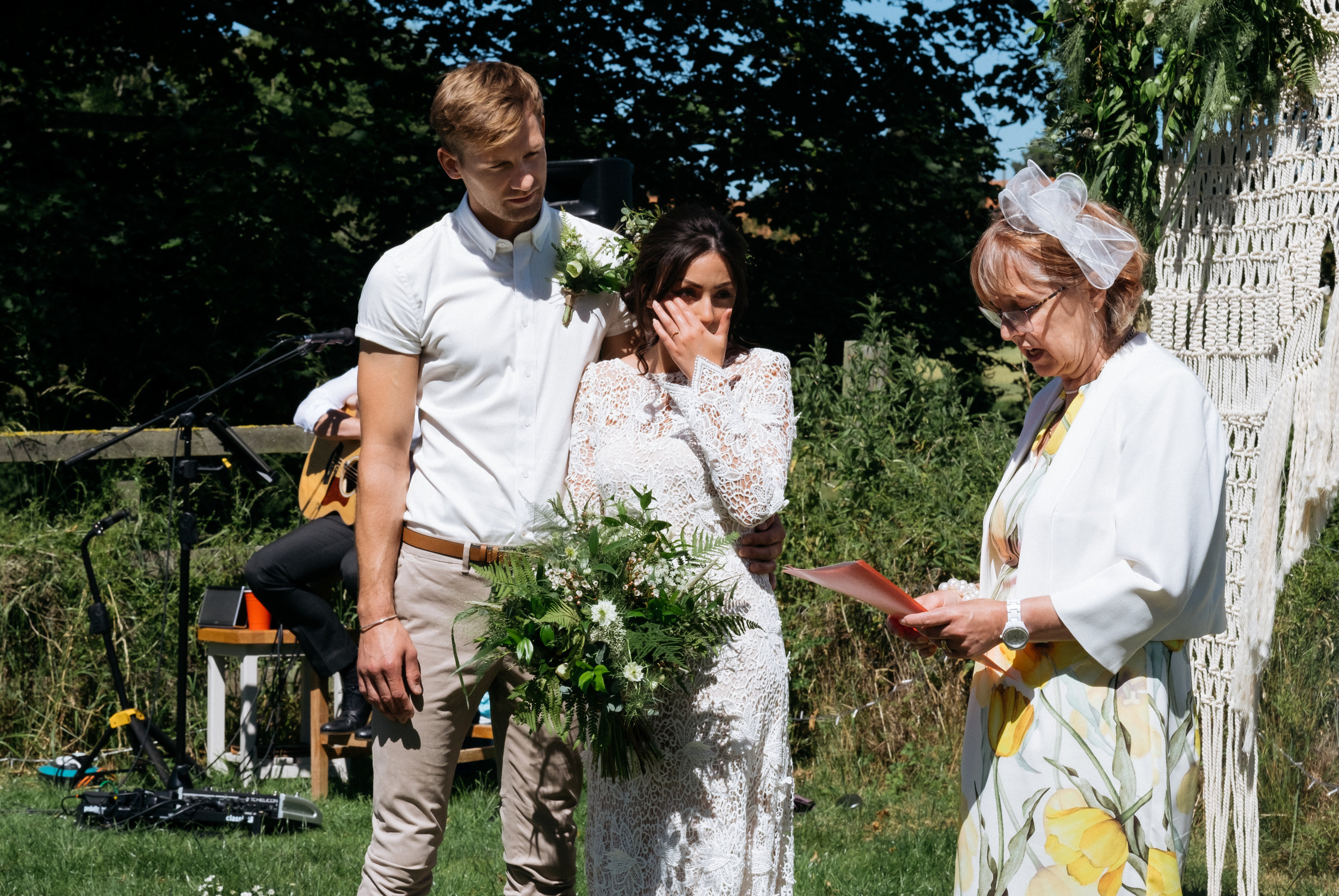 Bride and groom showing emotion while mother of the groom does a reading