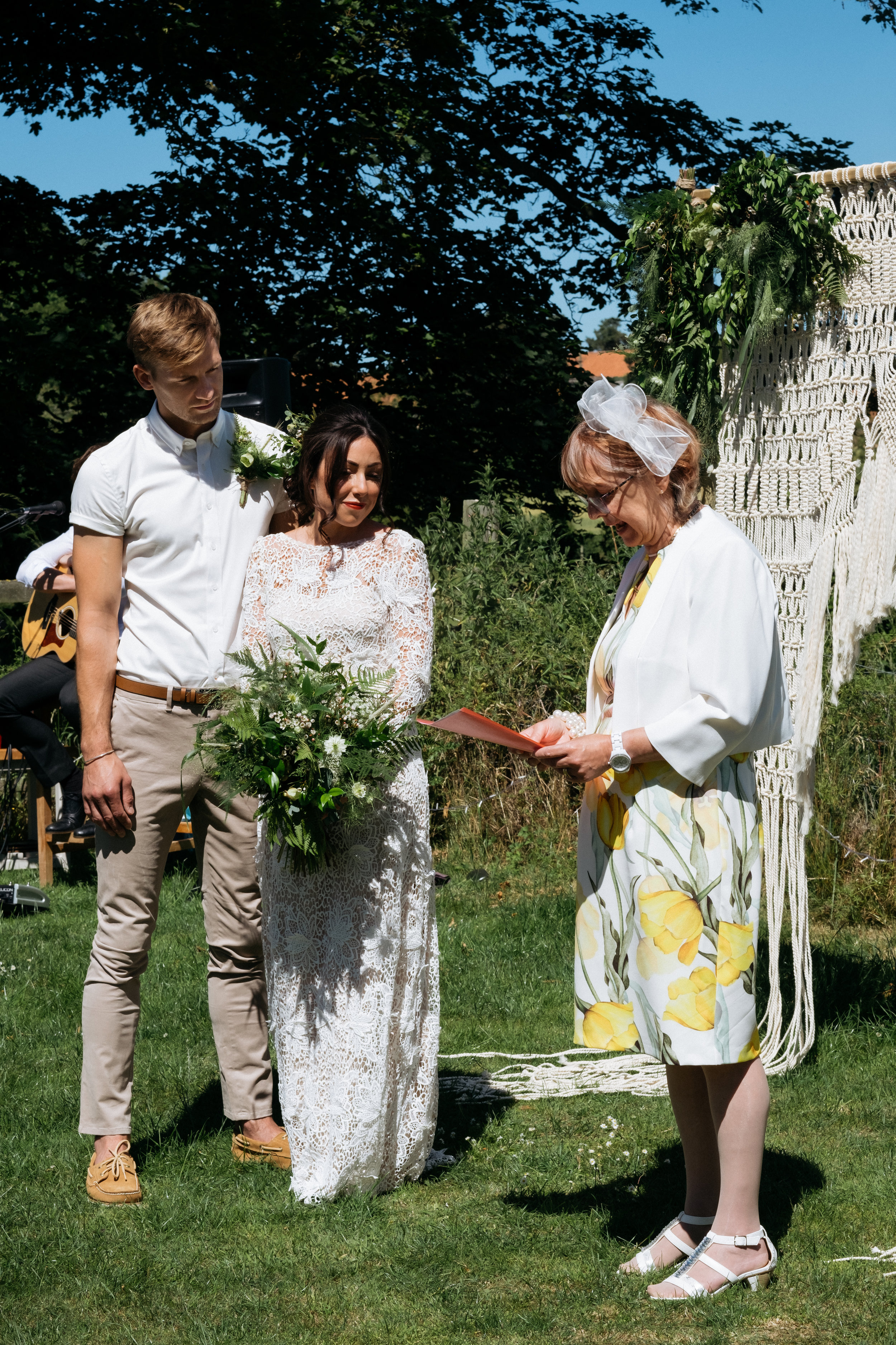 Bride and groom smiling through outdoor wedding ceremony reading