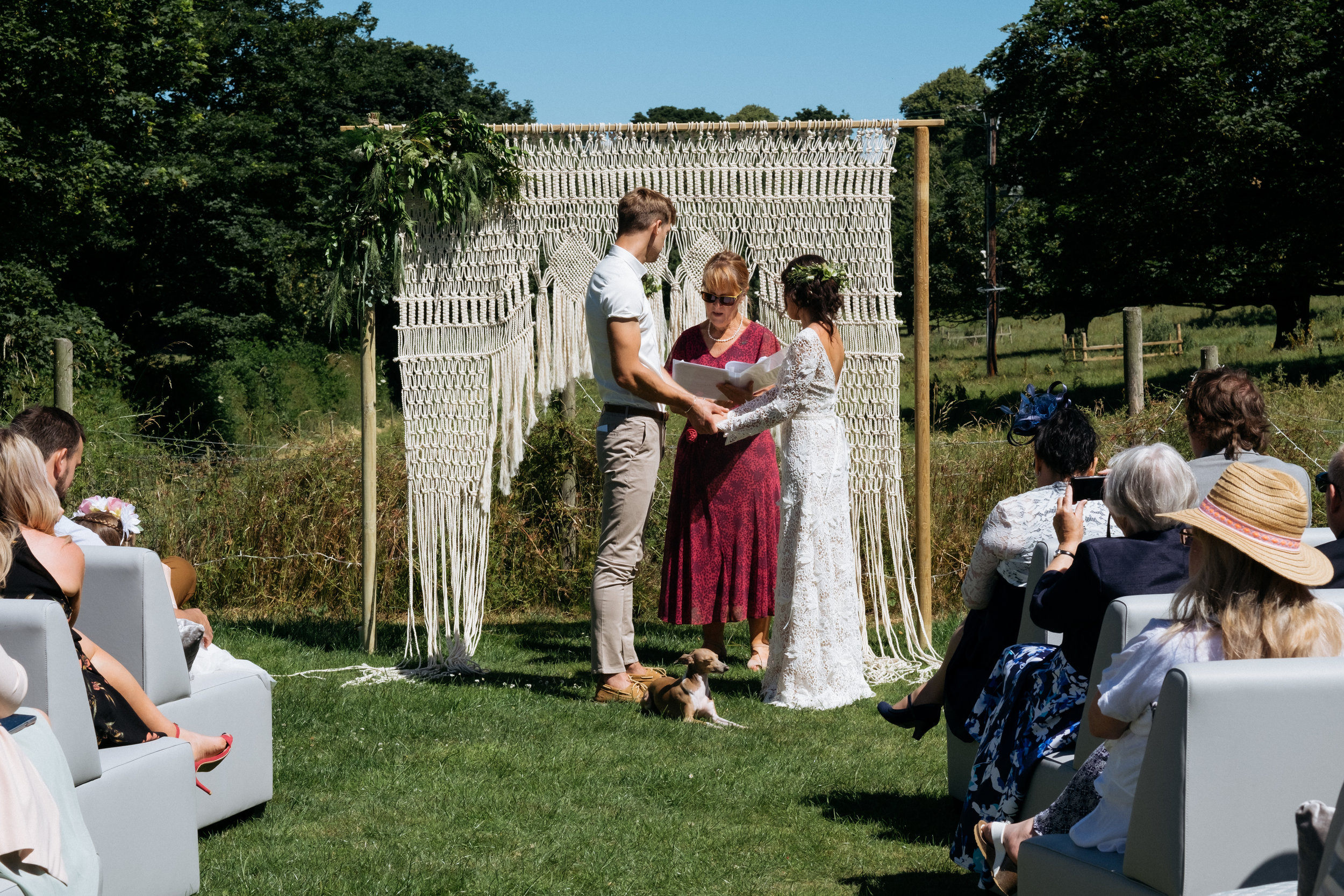 Bride and groom exchanging vows during outdoor wedding ceremony with macrame wedding arch and countryside views