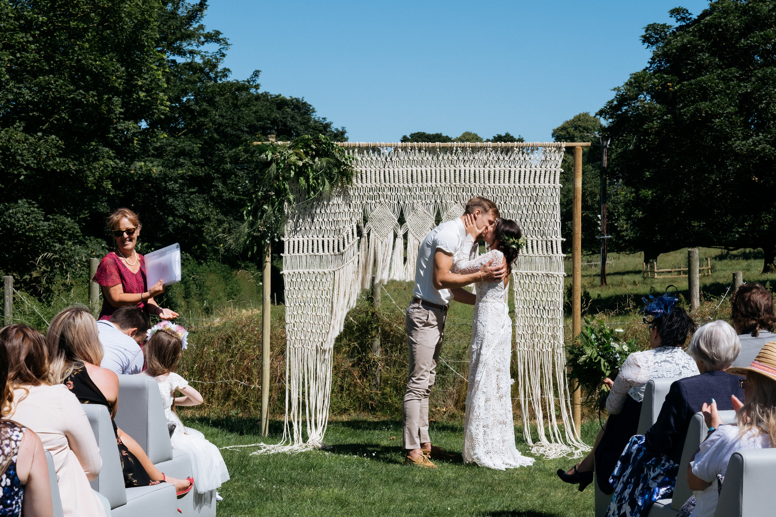Couple's first kiss as husband and wife | outdoor wedding ceremony in Lincolnshire with macrame wedding arch