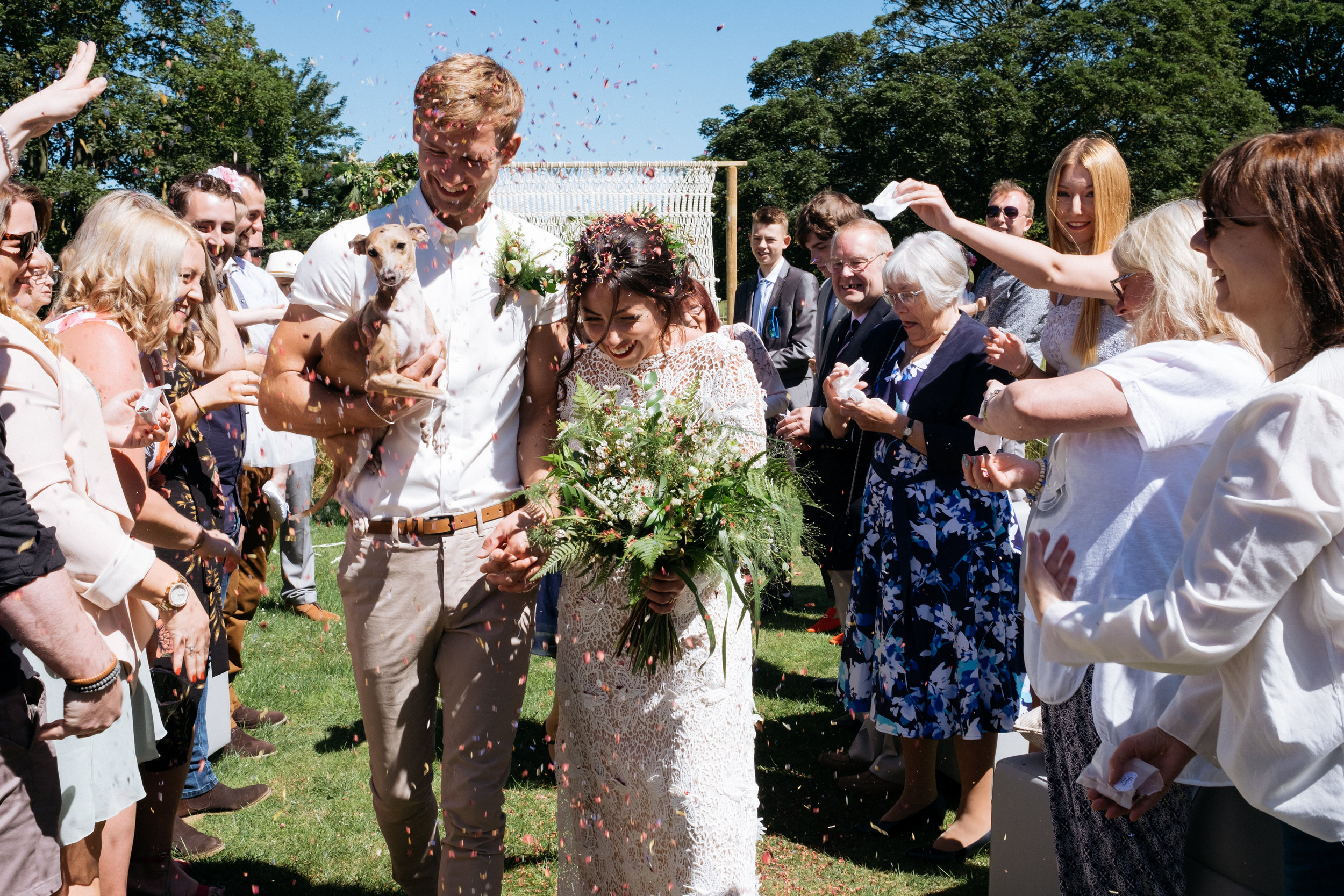 Bride and groom get confetti thrown at them