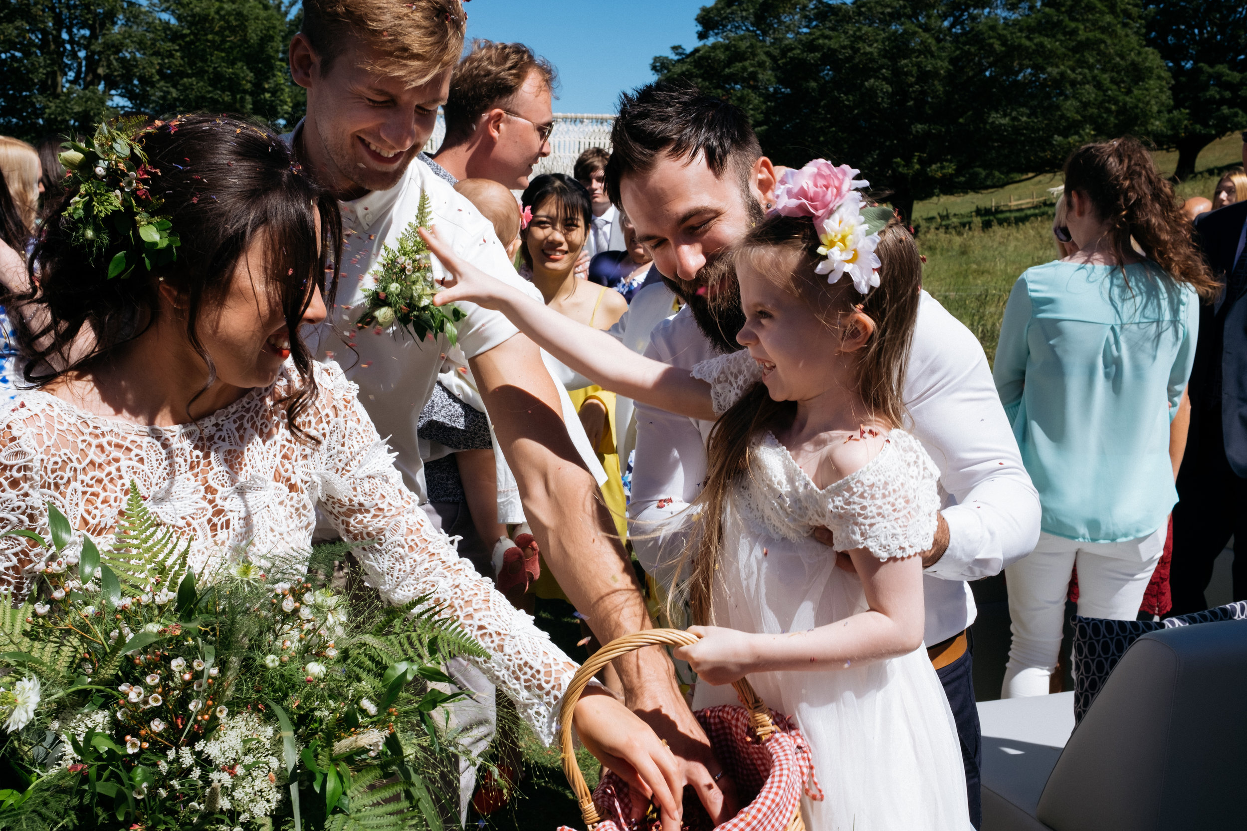 Flower girl throws confetti over bride