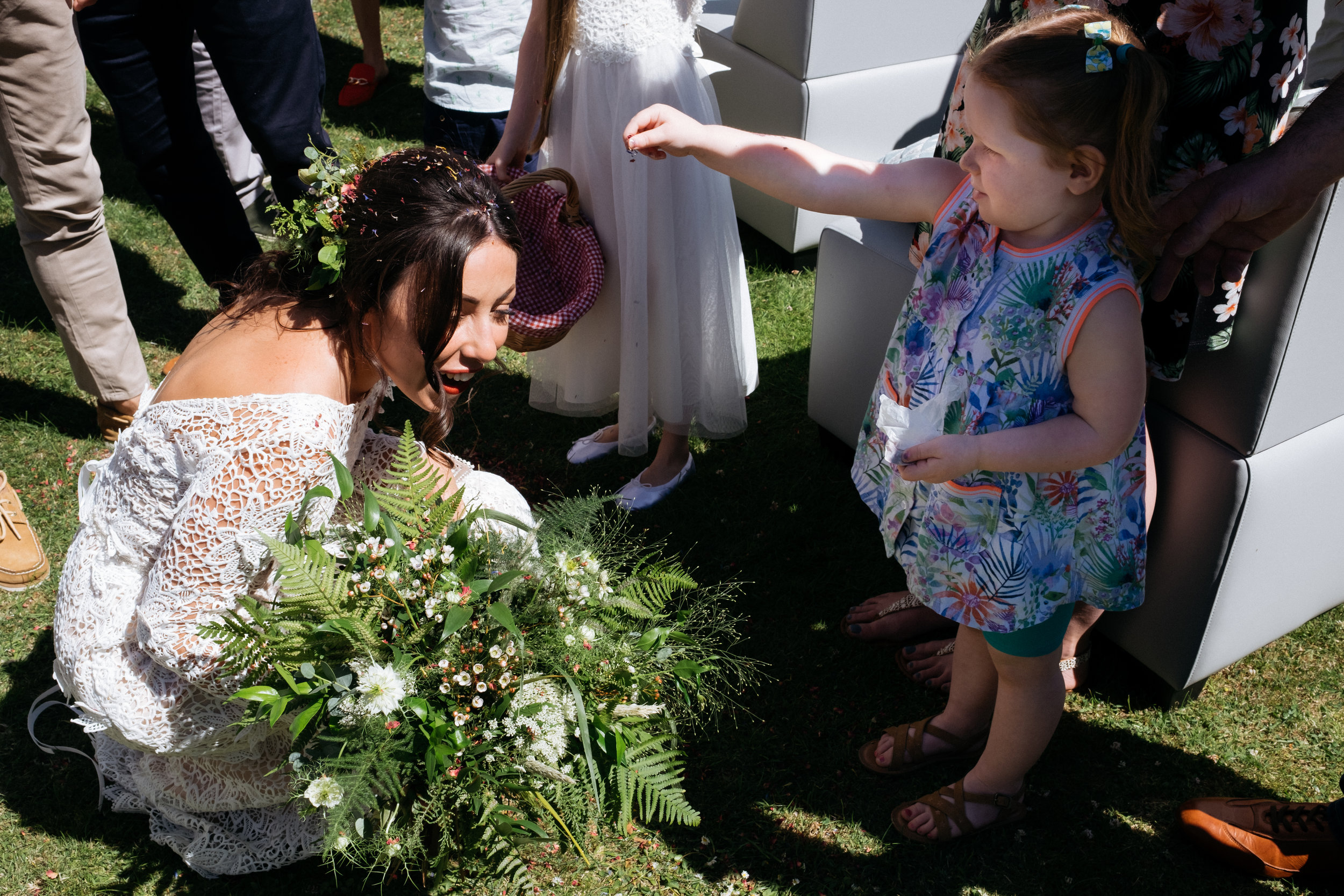 Toddler throwing confetti over the bride