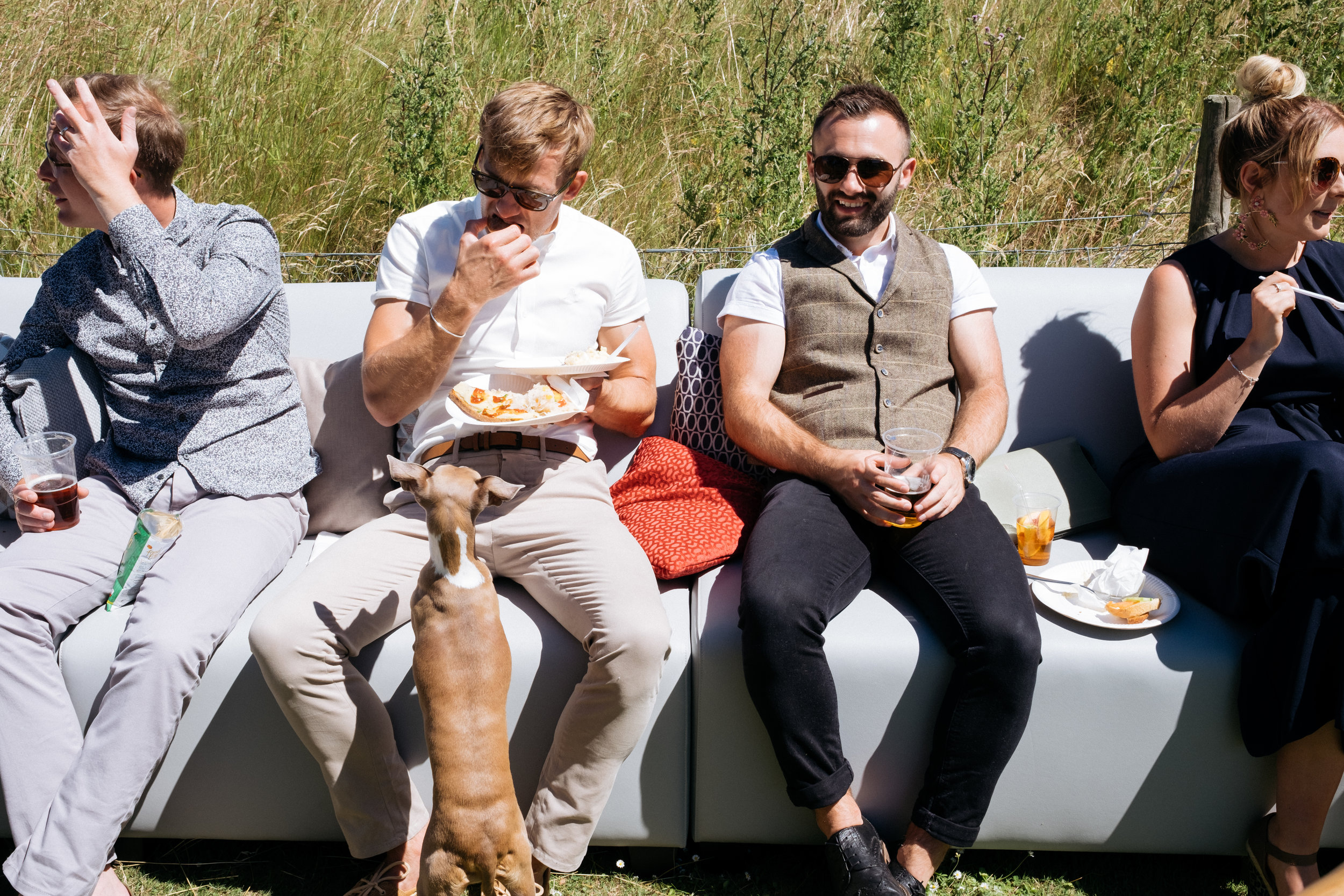 Groom eating while dog begs for food