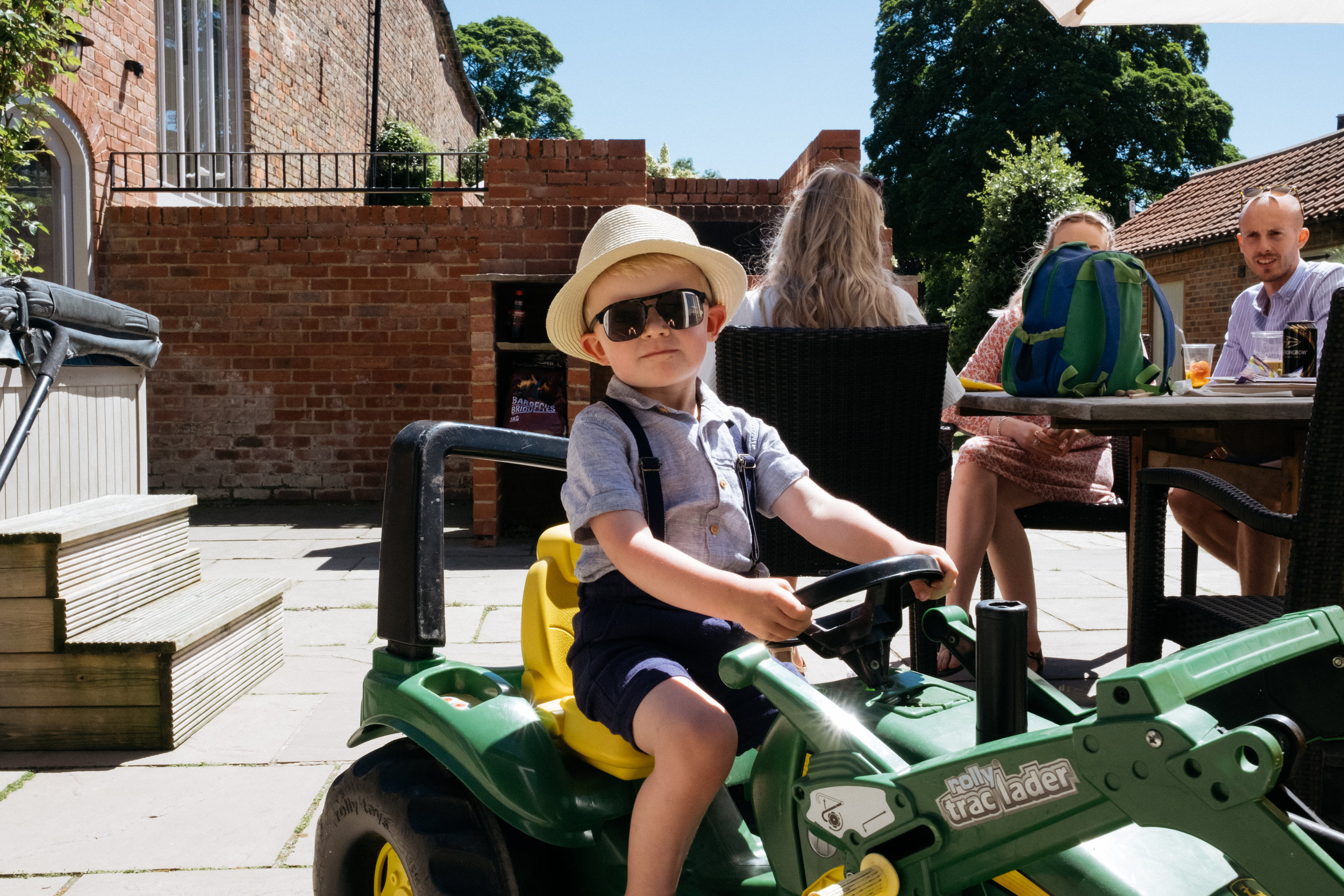 Young boy riding children's tractor wearing sunglasses