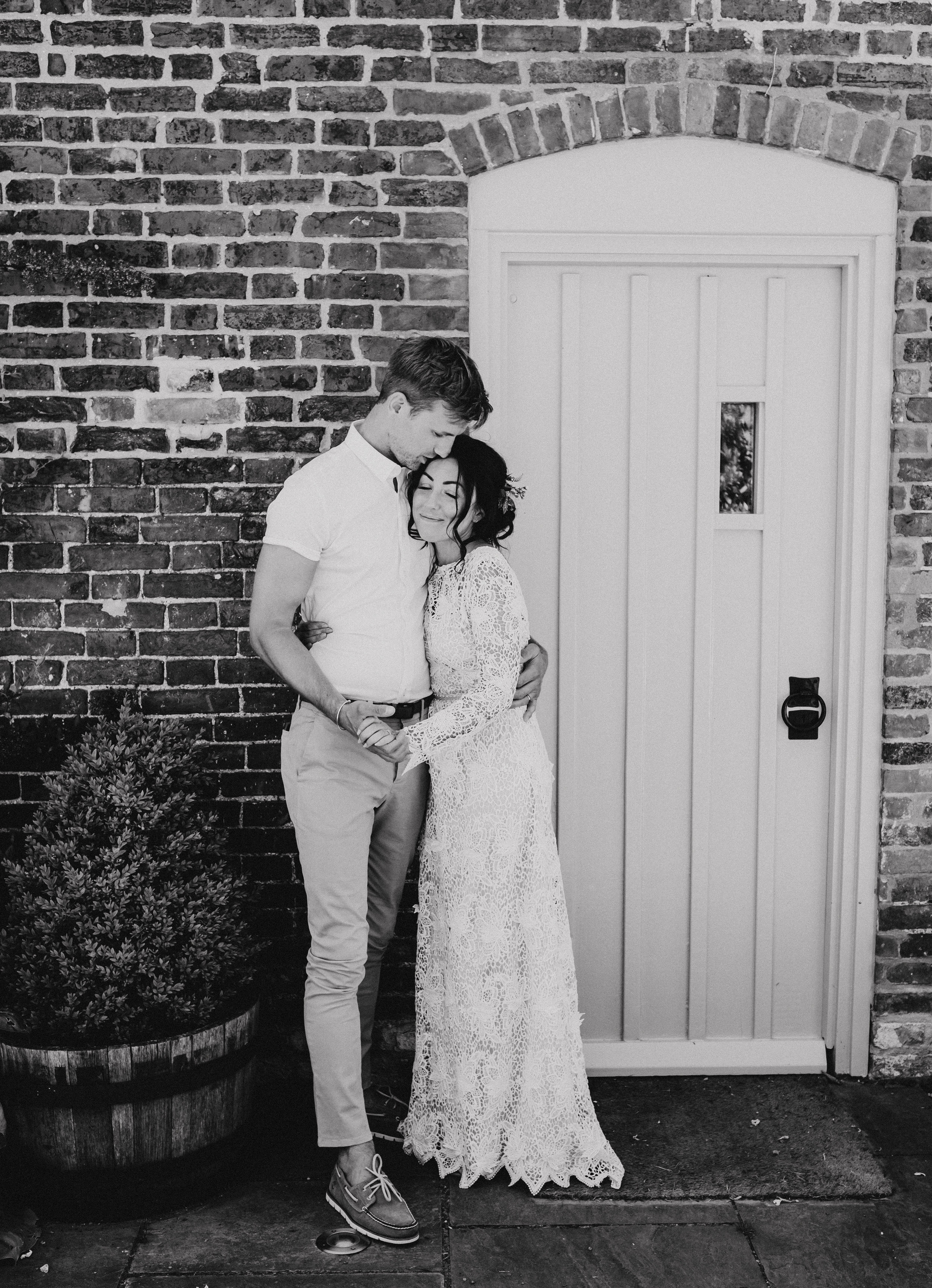 Groom kissing bride on the head | Black and white photograph