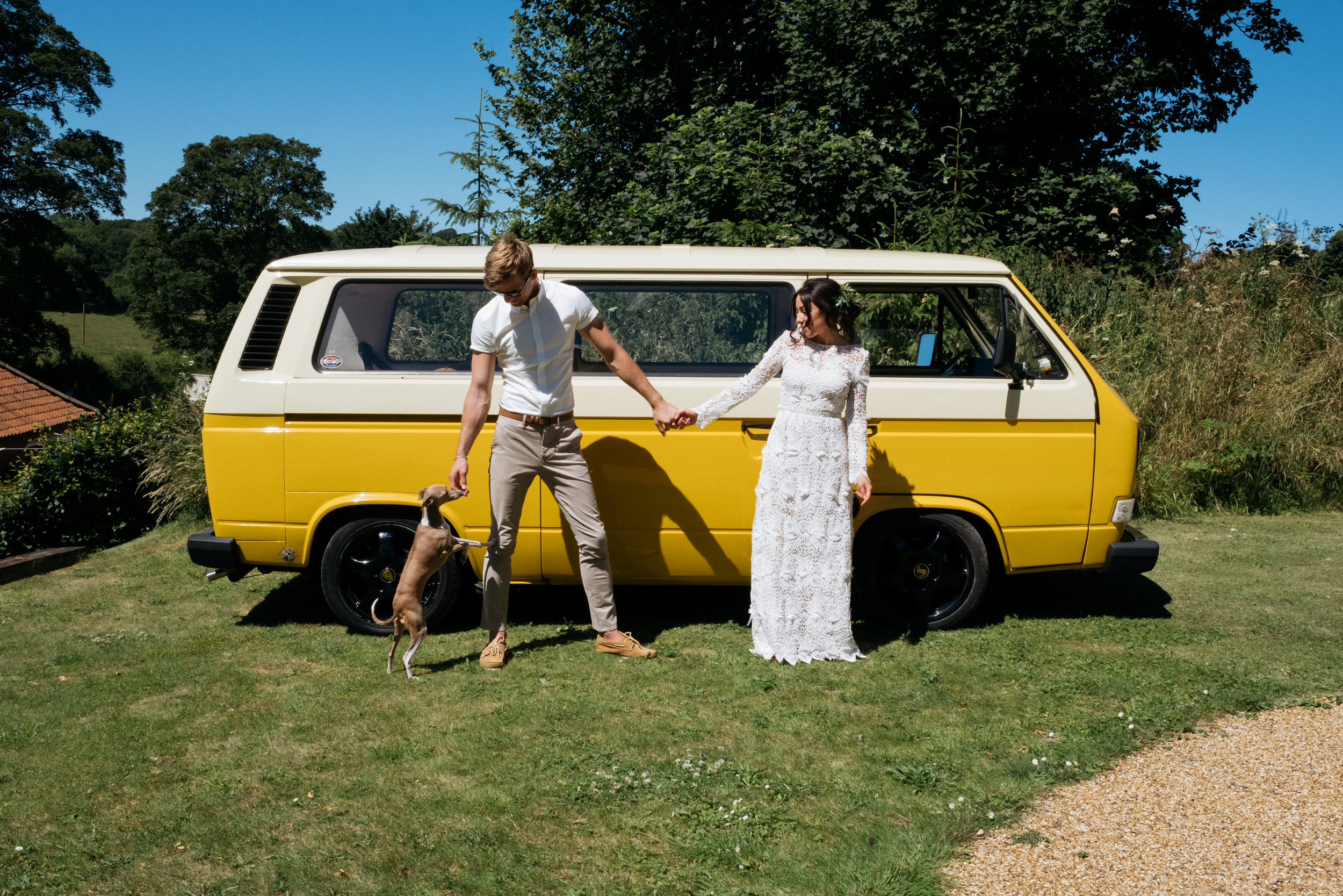 Bride and groom with VW camper van on wedding day