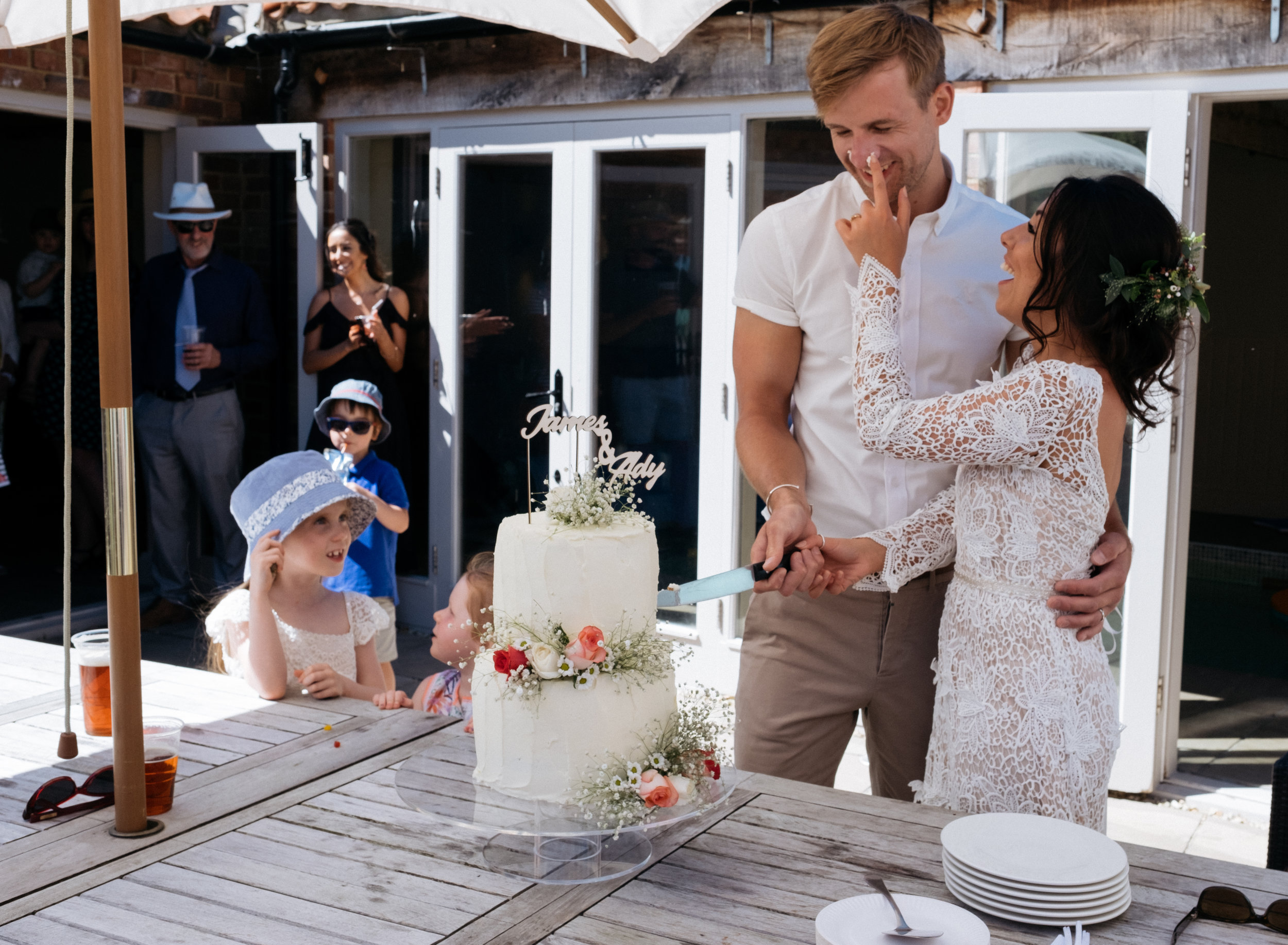Bride smashing cake on groom's face during cake cutting