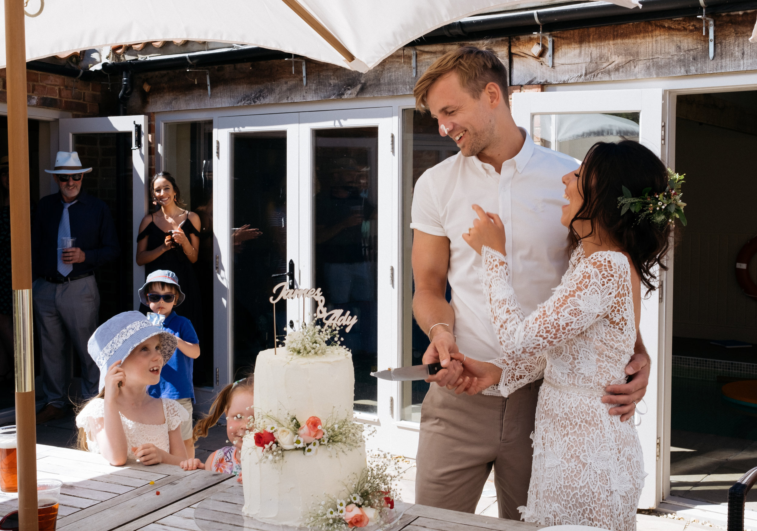 Bride and groom laughing during cake cutting