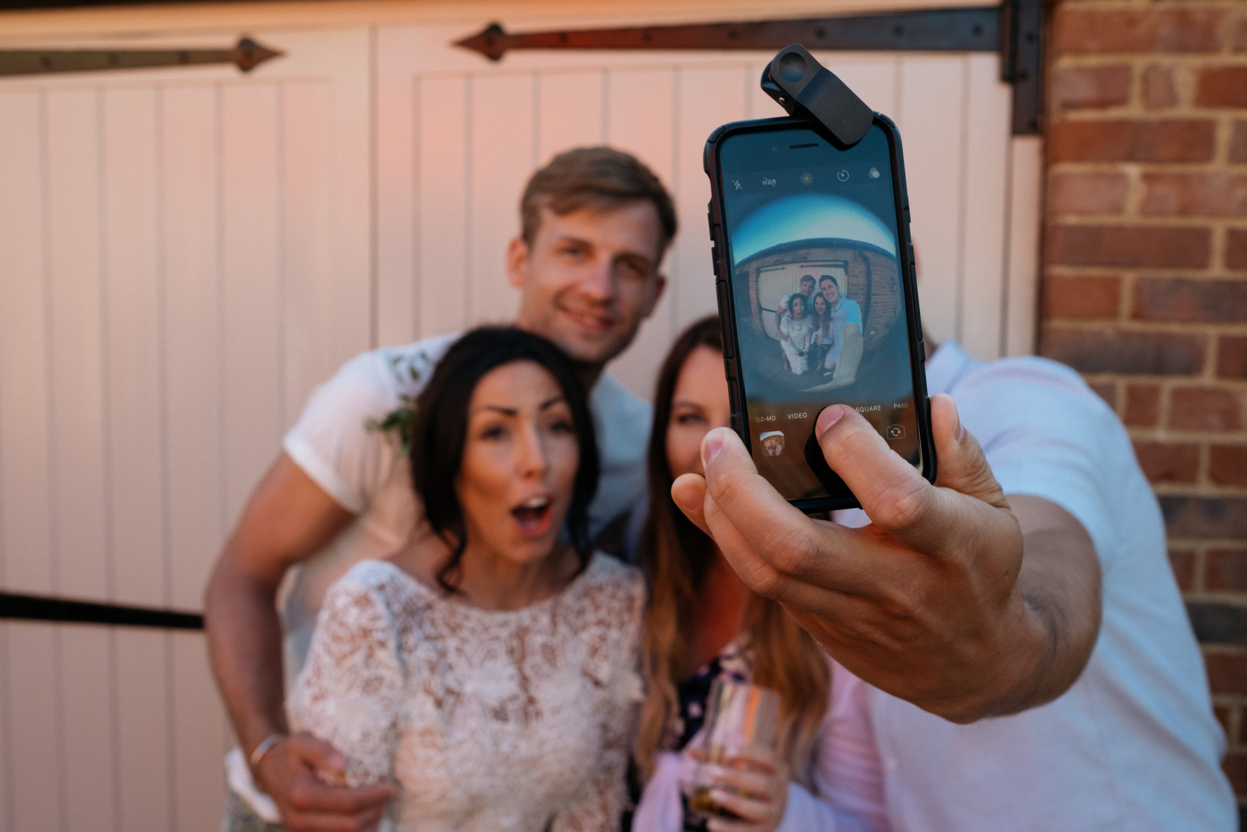 Bride and groom doing selfie with wedding guests
