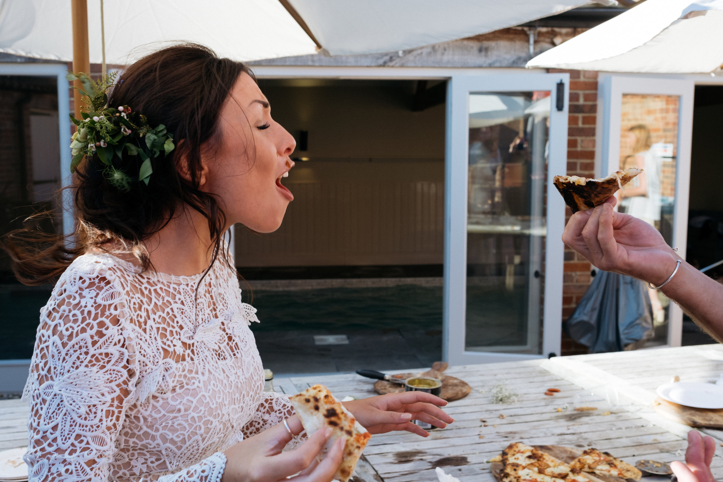 Bride reacts to having pizza smashed in her face during wedding reception