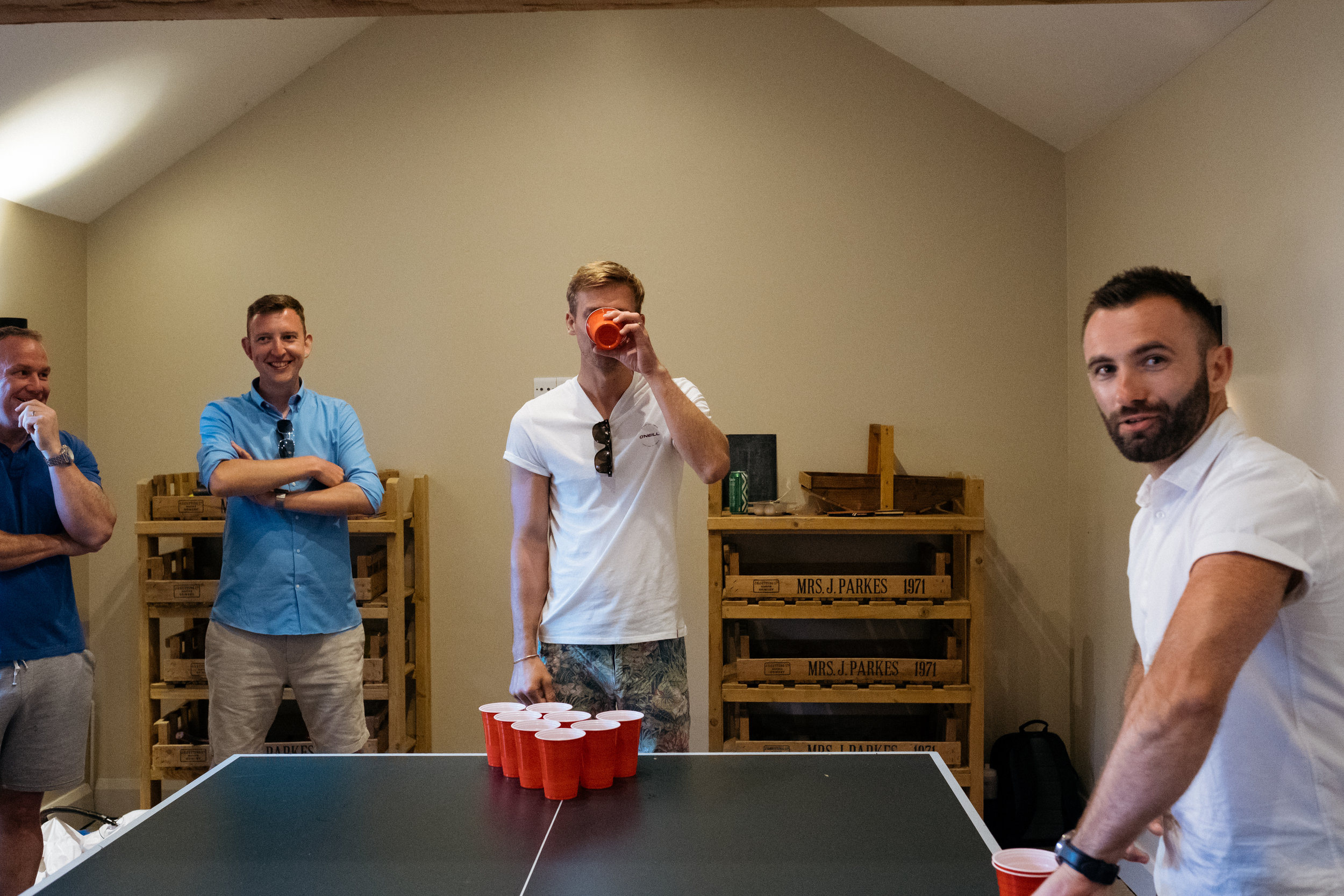 Groom drinks in beer pong at wedding