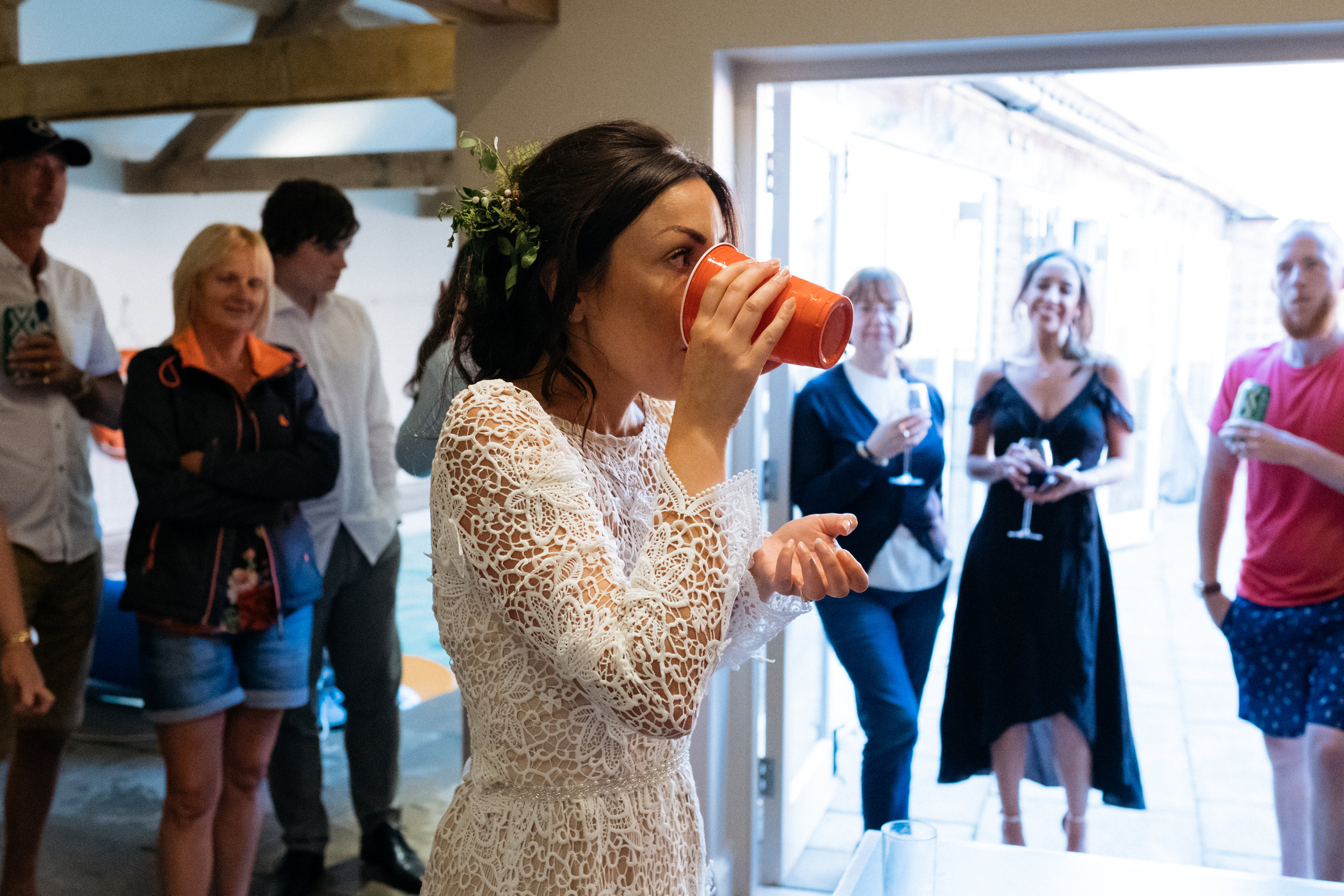 Bride drinks in wedding beer pong