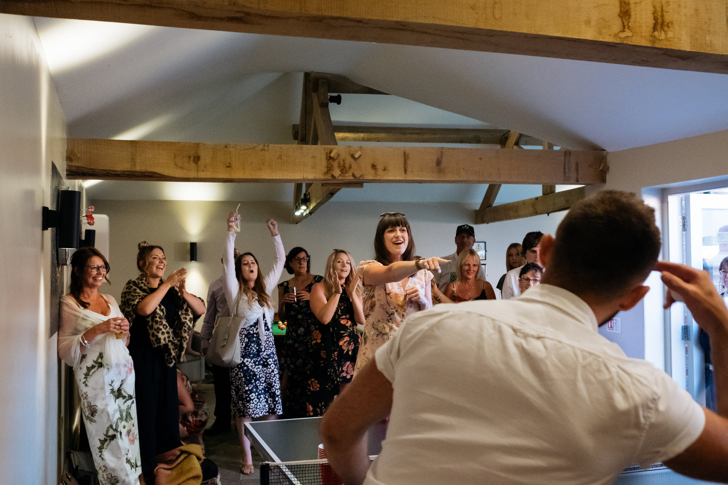 Wedding guests celebrate during beer pong