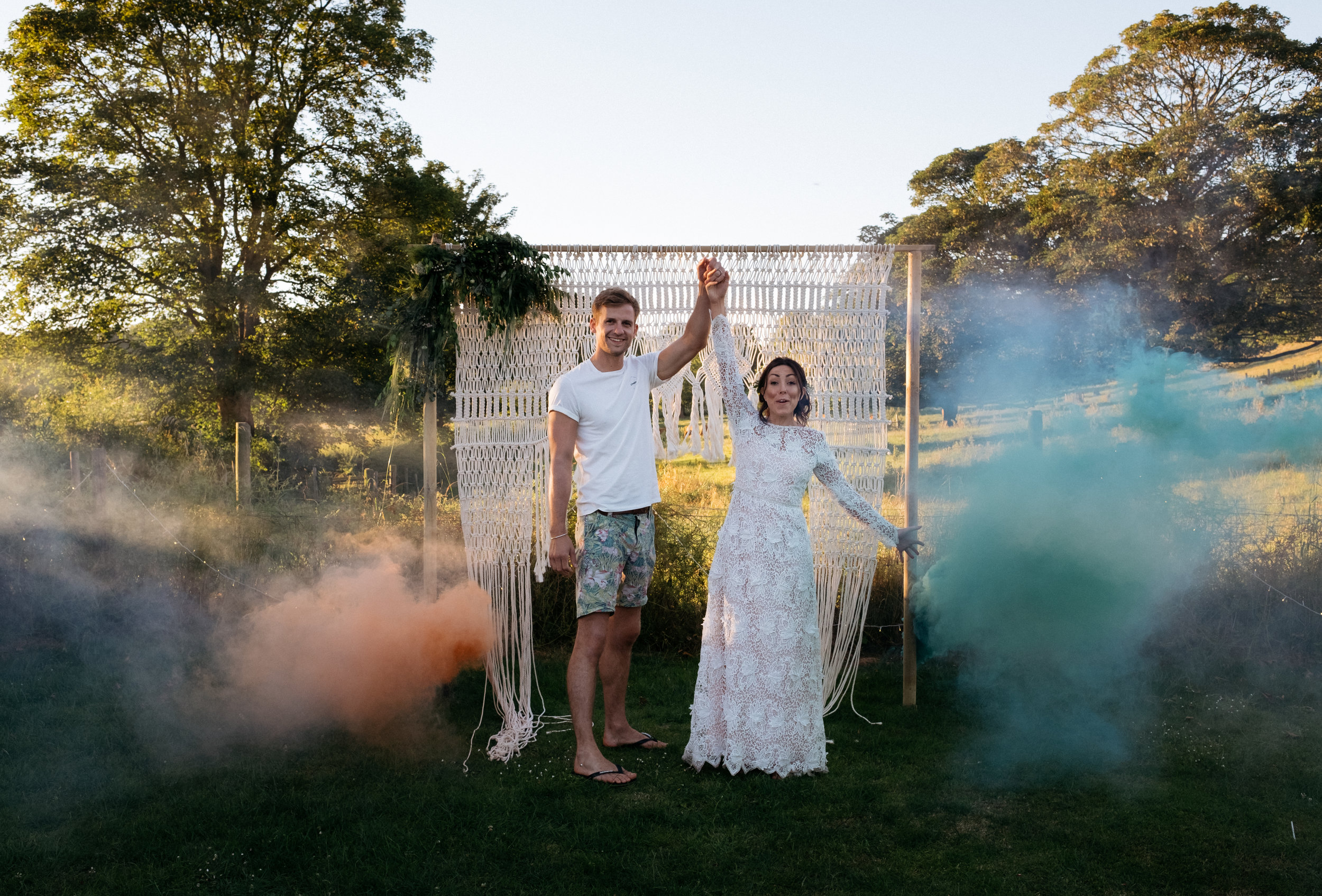 Bride and groom with coloured smoke grenades on wedding day