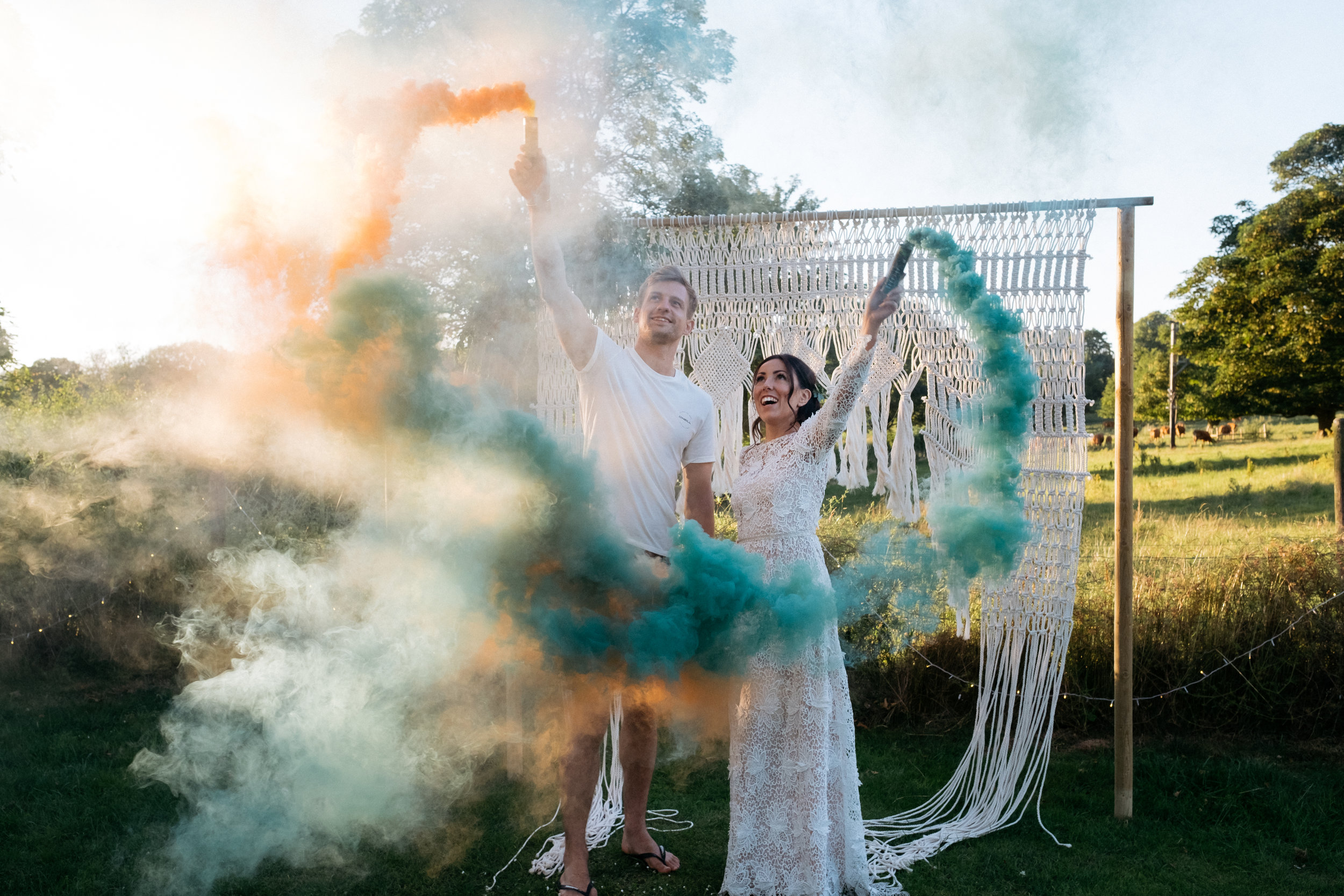 Bride and groom drawing heart with smoke grenades on wedding day