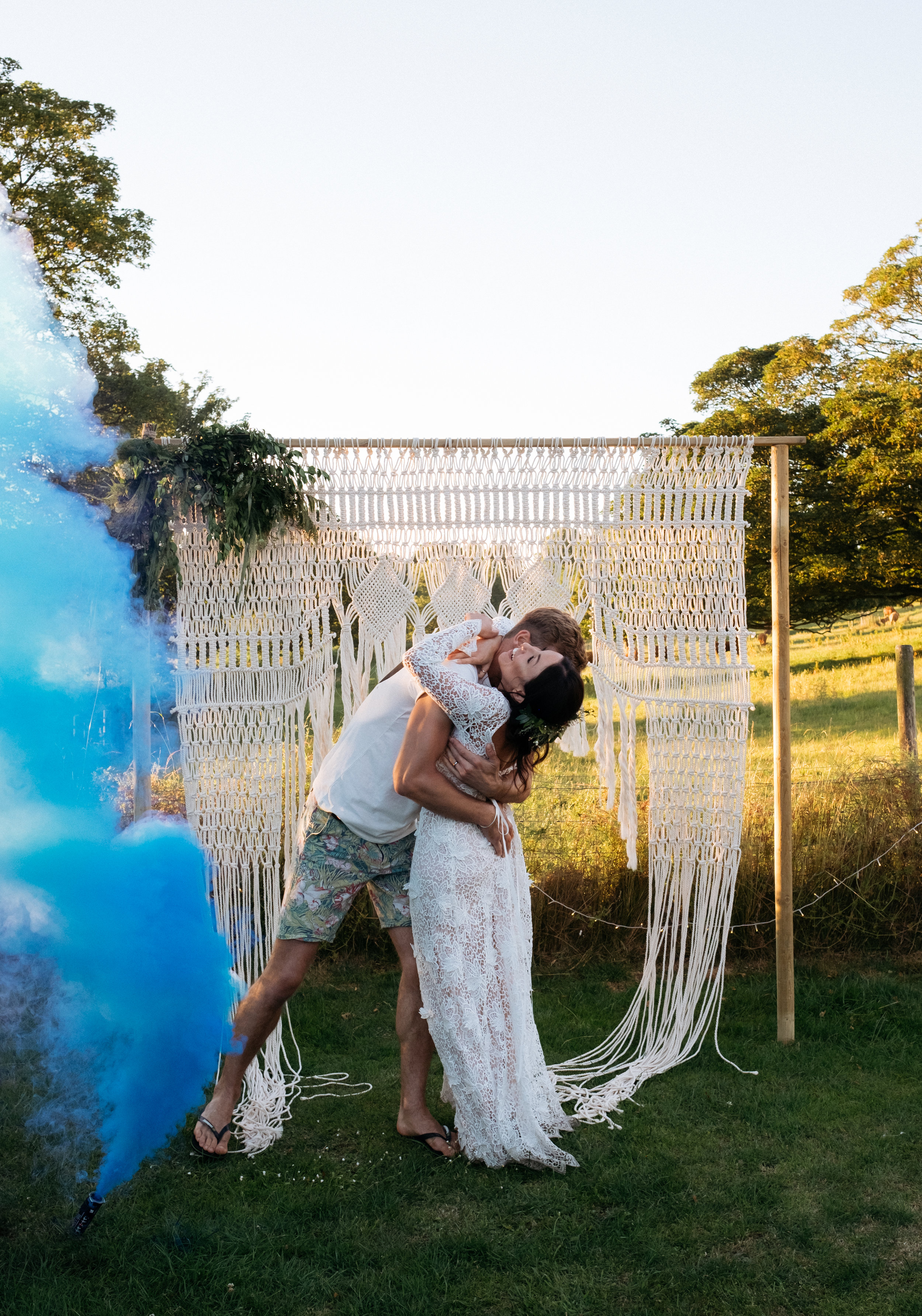 Bride and groom cuddling with smoke grenade to the side