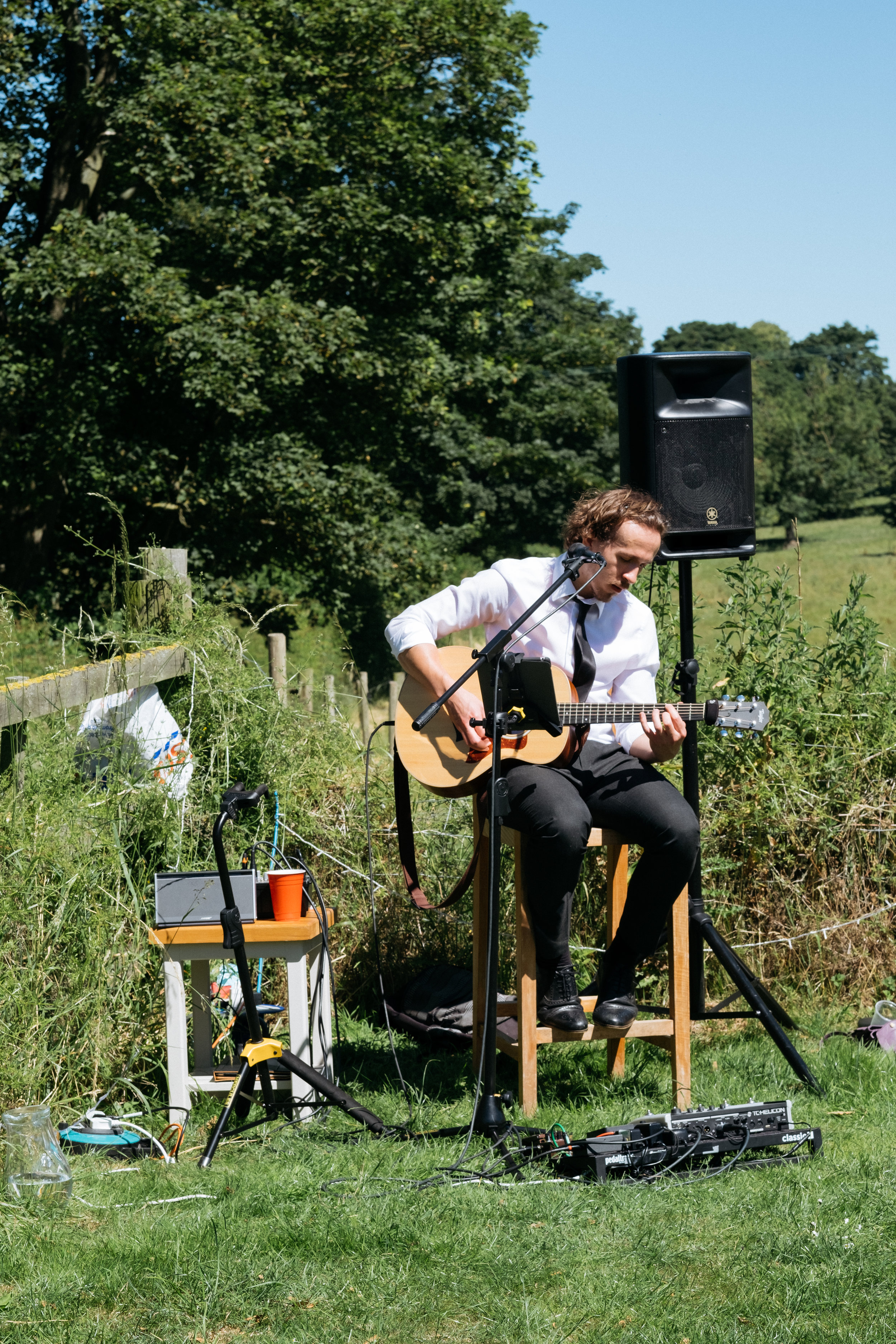 Acoustic musician Sam Dawson playing at relaxed outdoor wedding