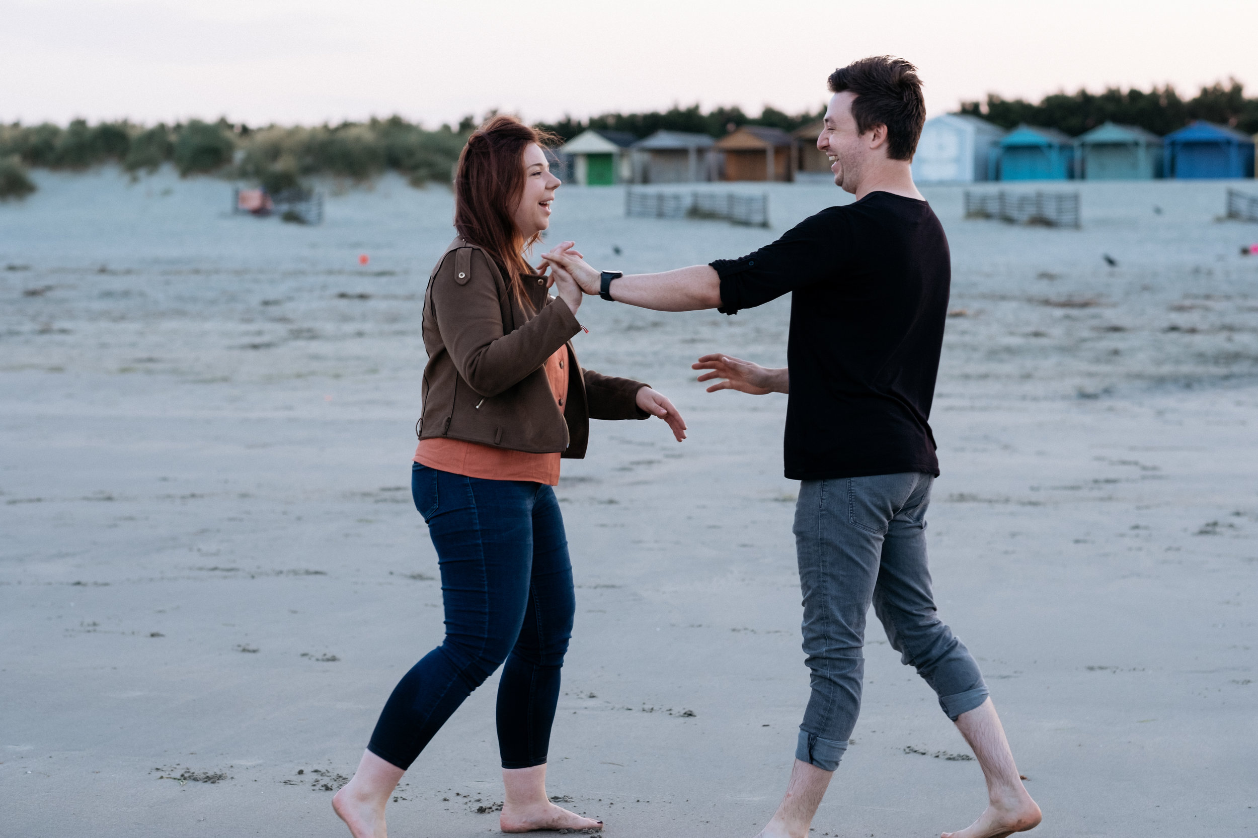 Couple laughing and playing around on West Wittering beach