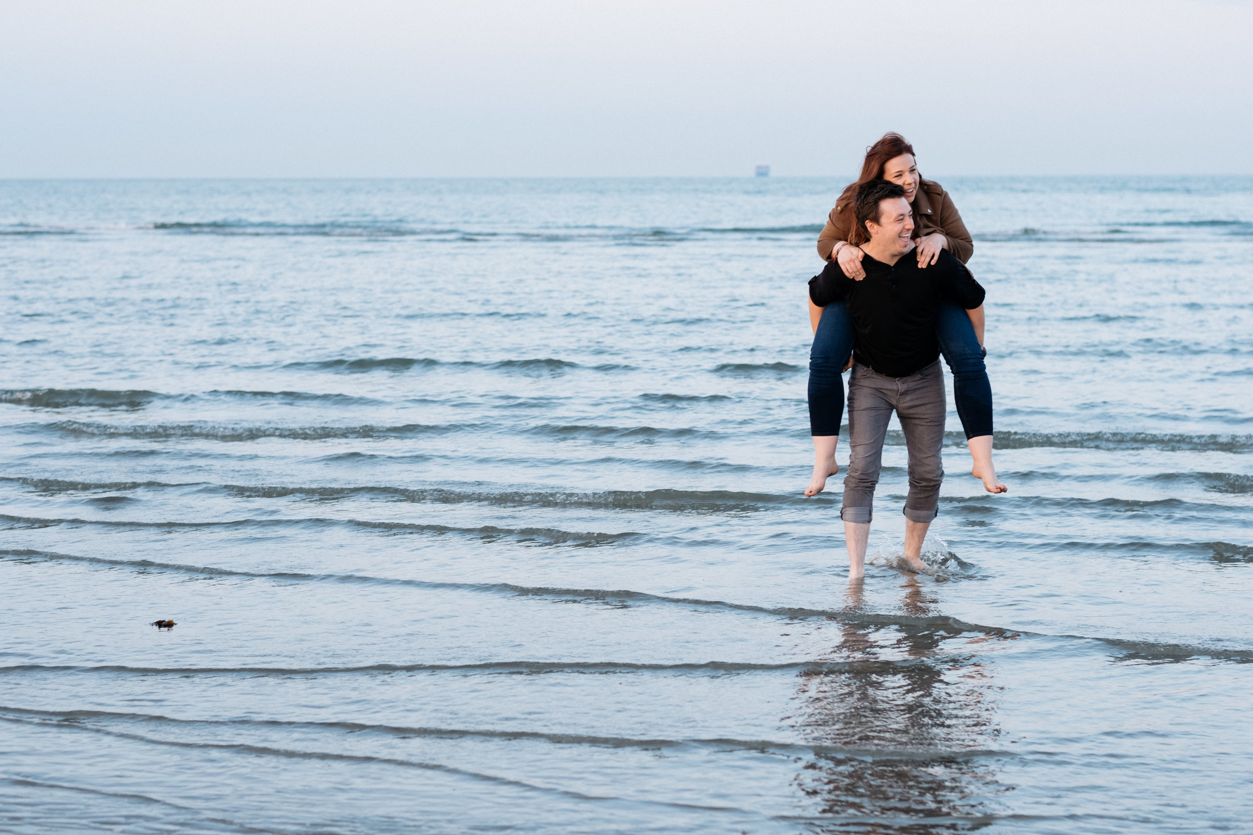 Piggyback in the sea during engagement shoot at West Wittering