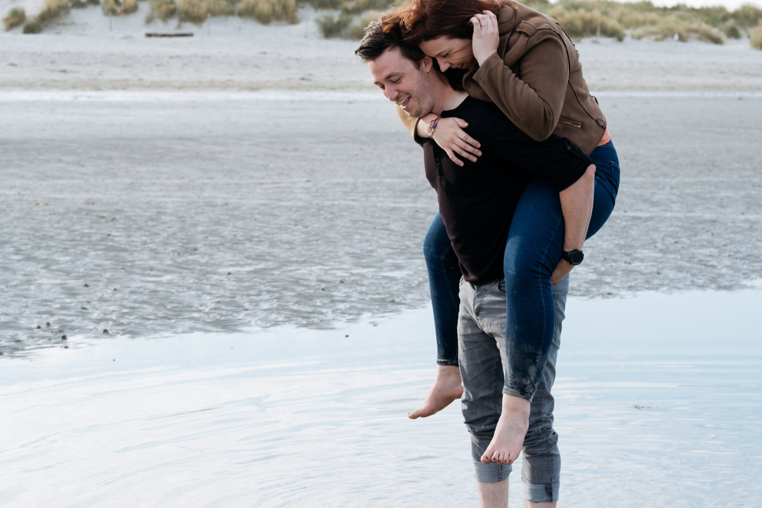 Couple piggyback in the ocean at West Wittering during engagement shoot