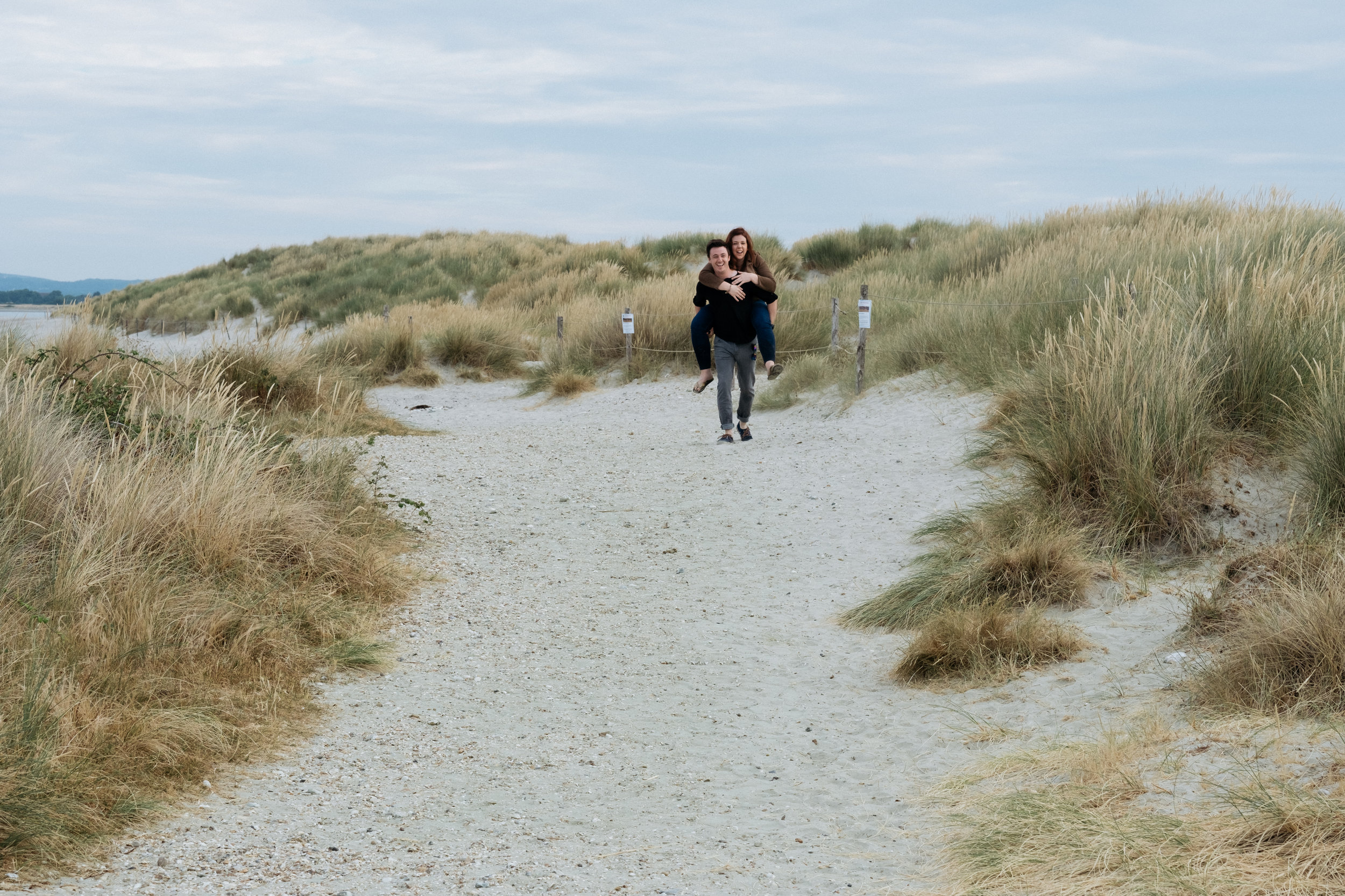 Couple piggyback through sand dunes at West Wittering