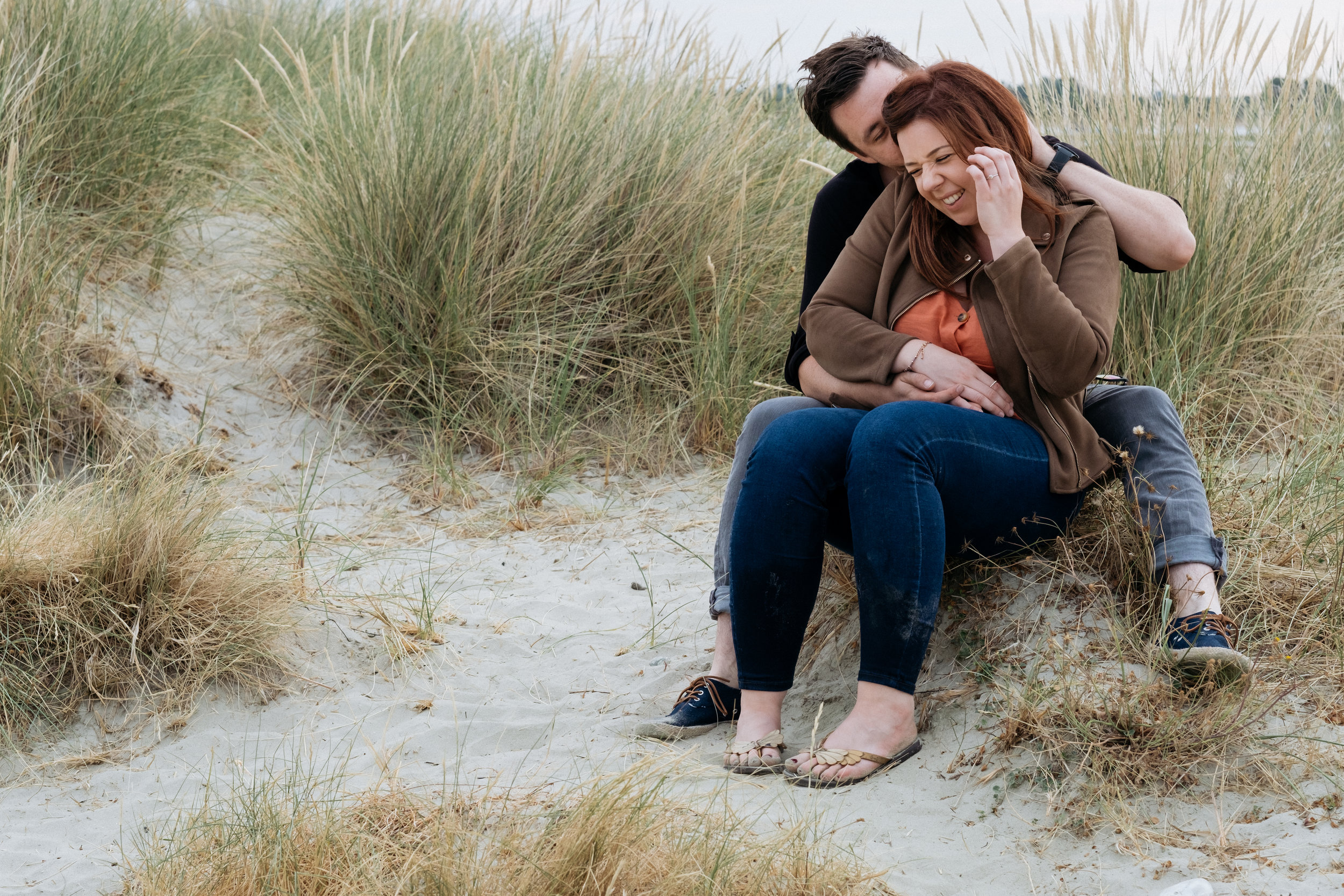 Couple laughing sat near the sand dunes at West Wittering beach