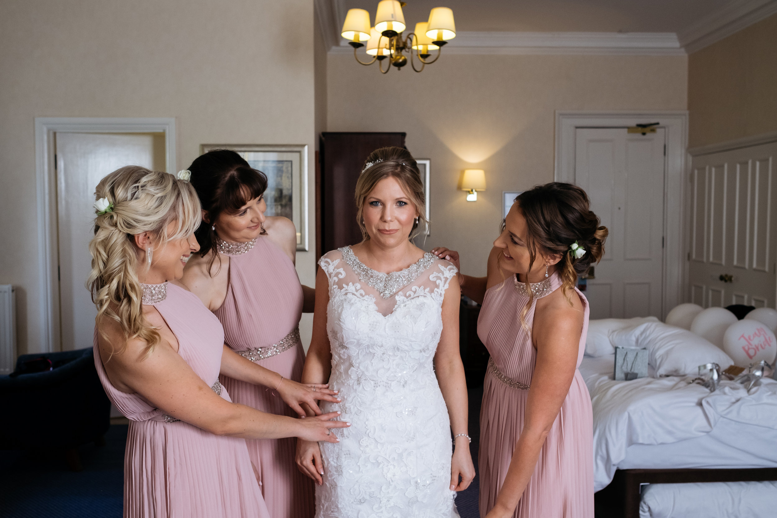 Bridesmaids helping bride get ready on morning of wedding