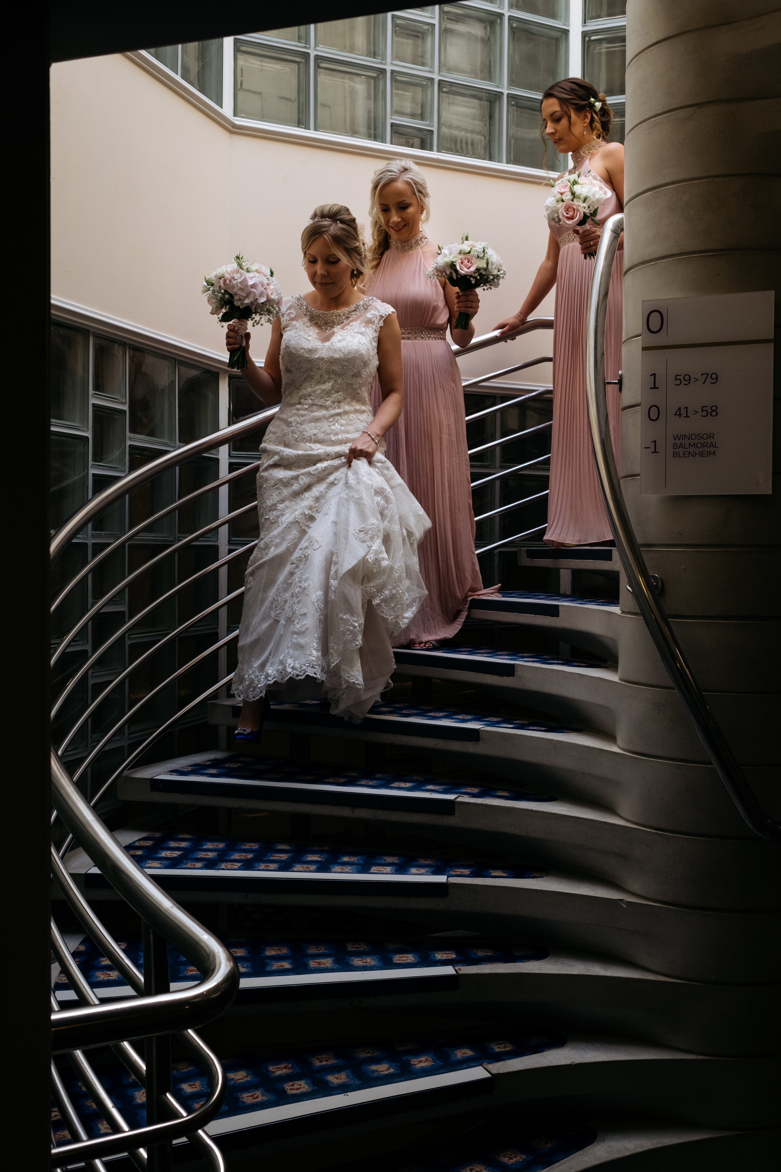 Bride and bridesmaids walking down spiral staircase on way to wedding ceremony