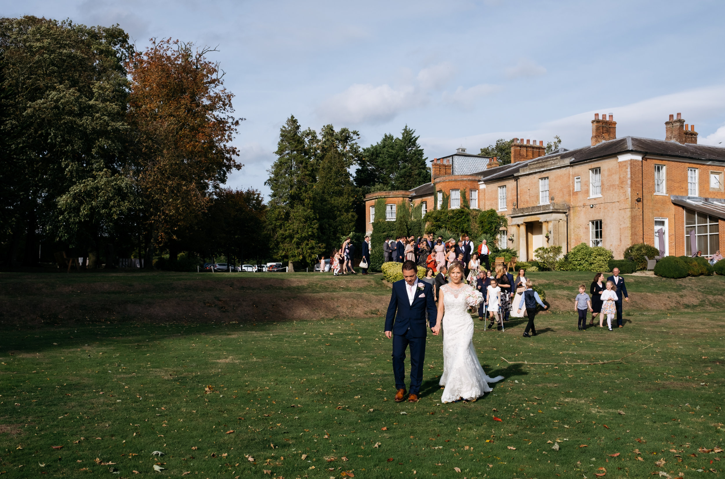Bride and Groom walking around the grounds at Mercure Newbury Elcot Park Hotel wedding