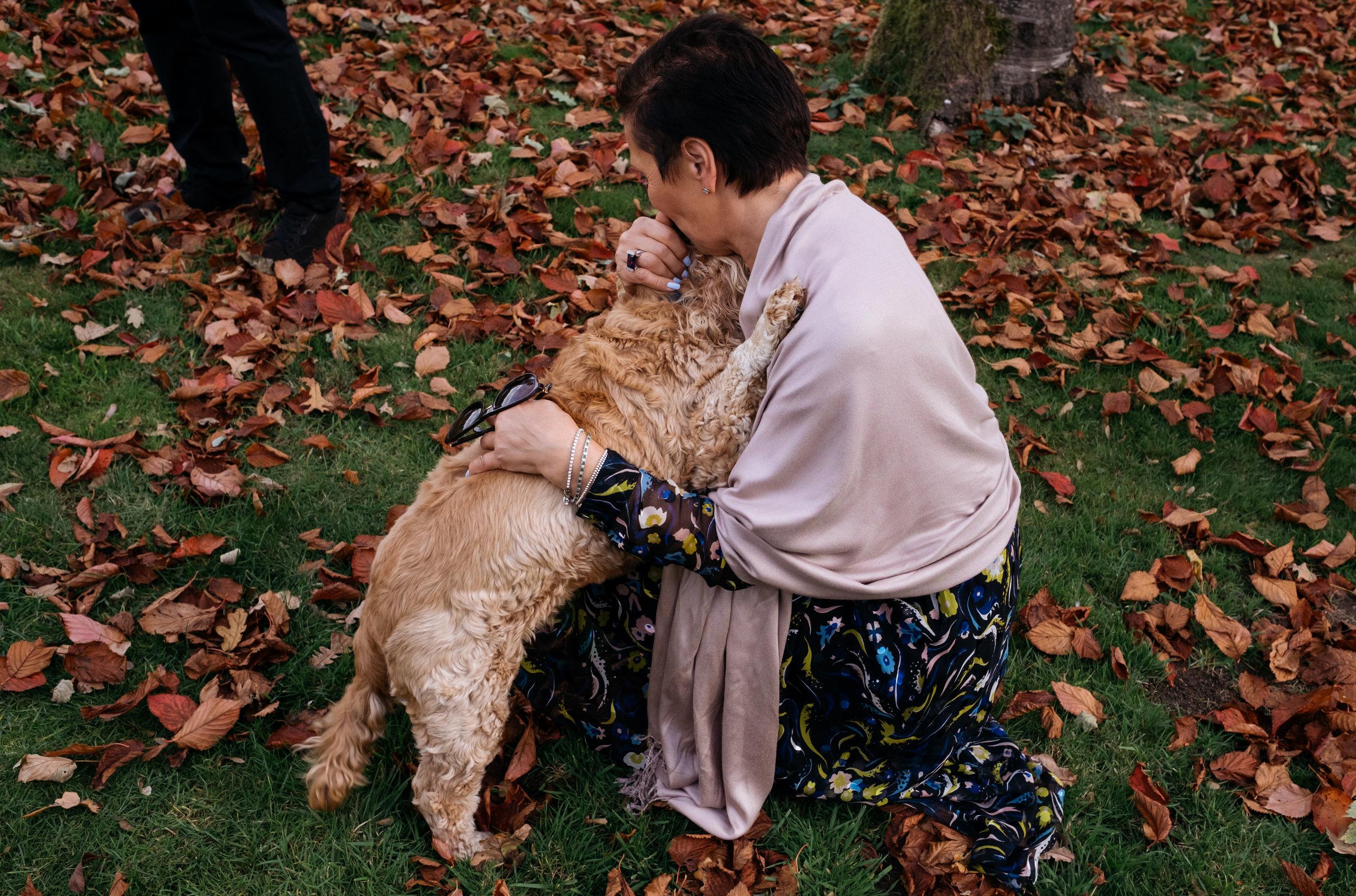 Wedding guest cuddling dog