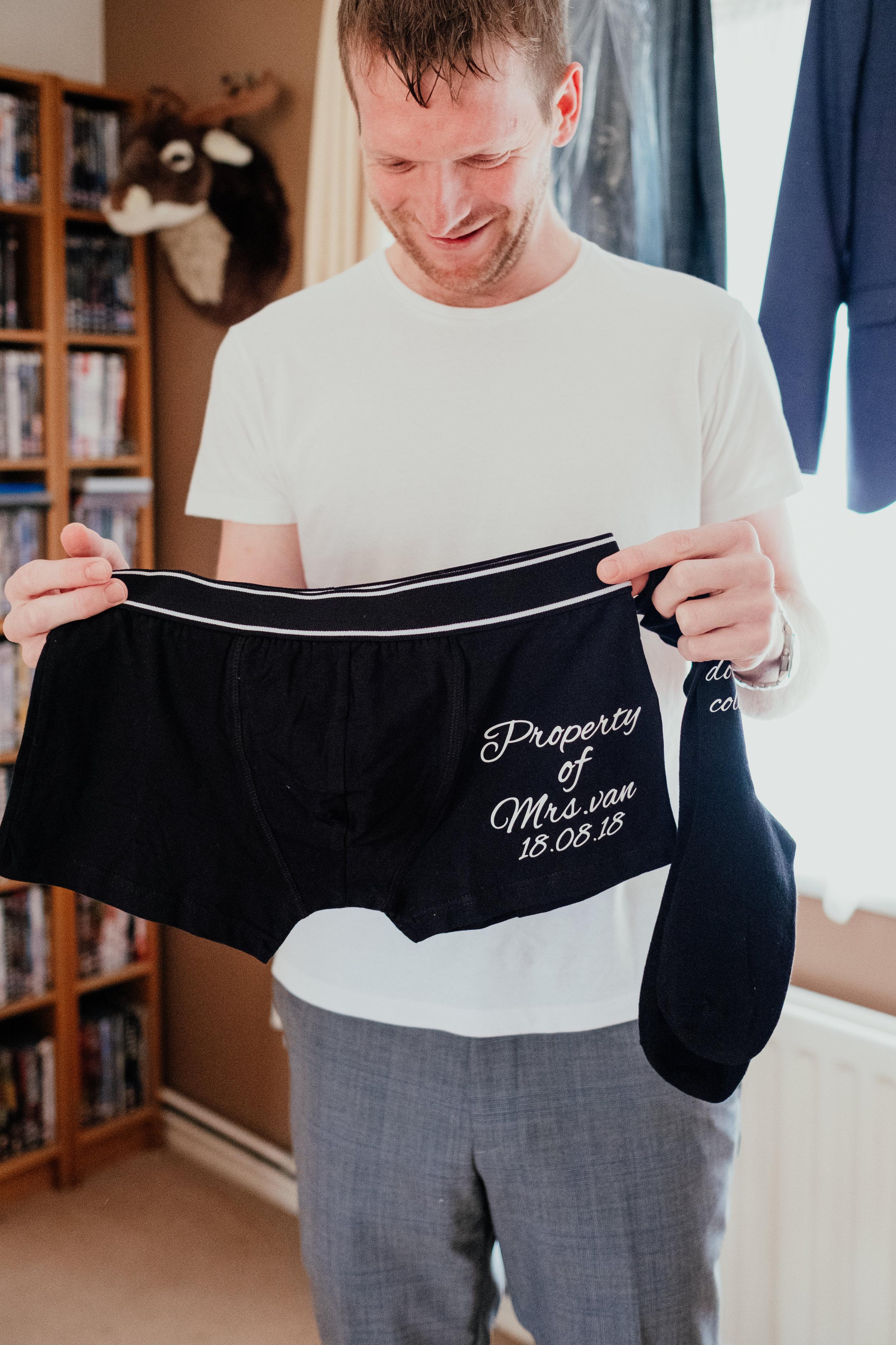 Groom holds wedding boxers