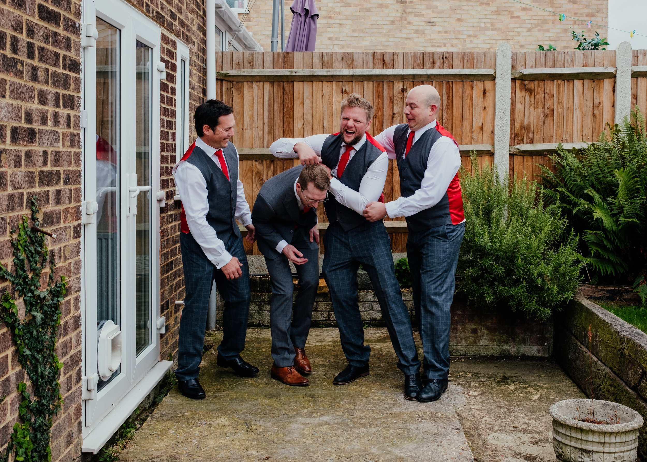 Groomsmen play fighting with groom