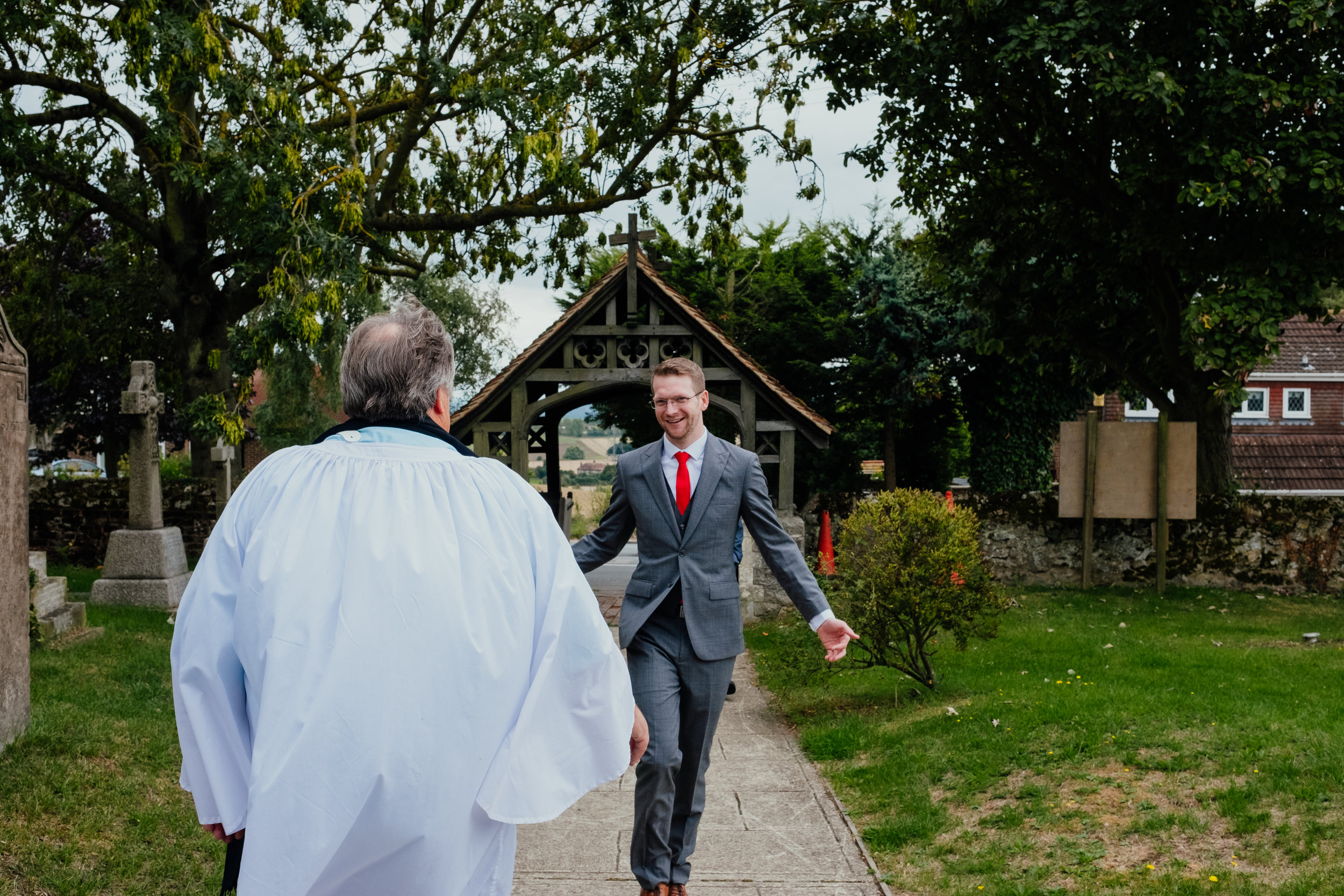 Groom walking towards priest and church