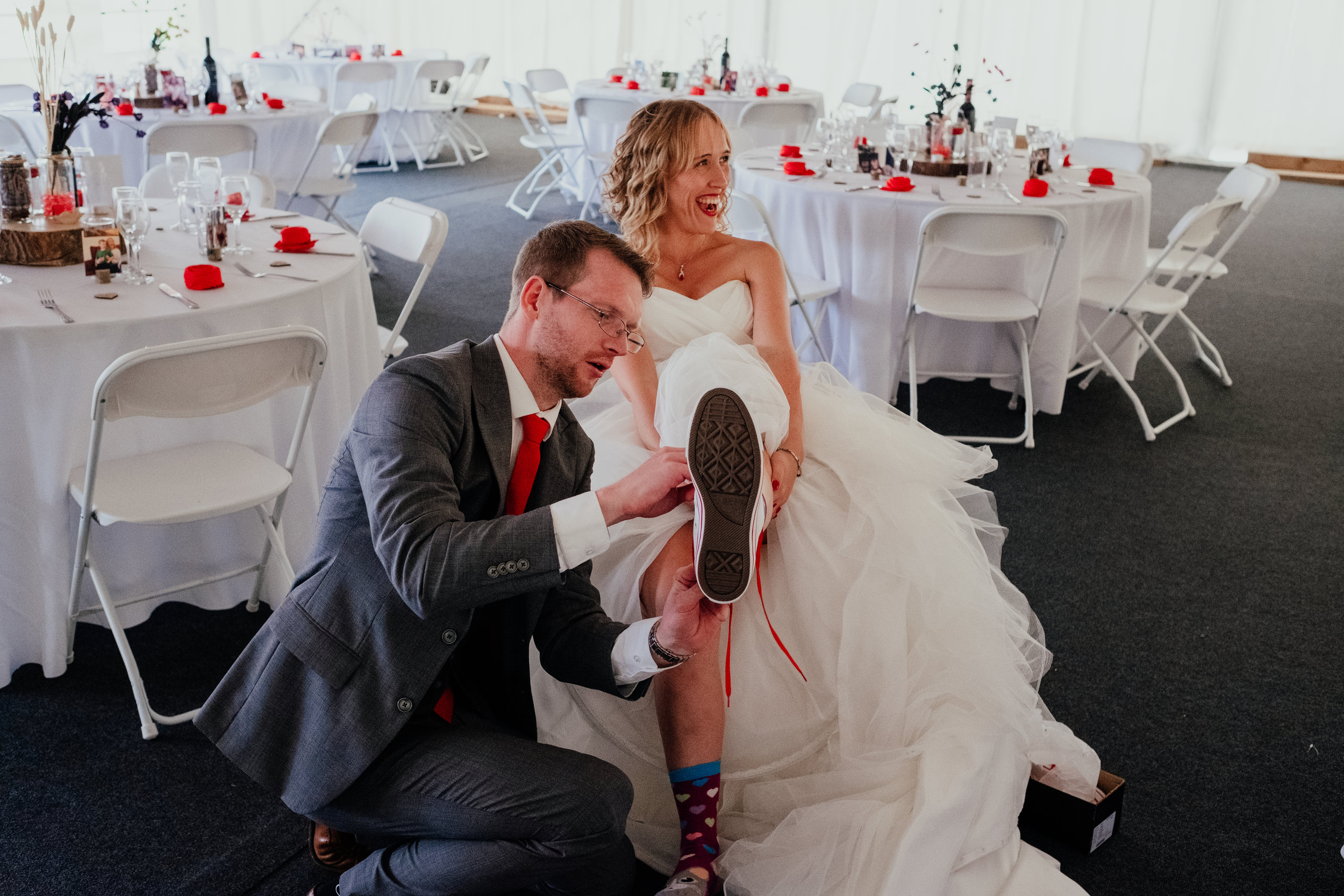 Bride and groom putting on wedding converse
