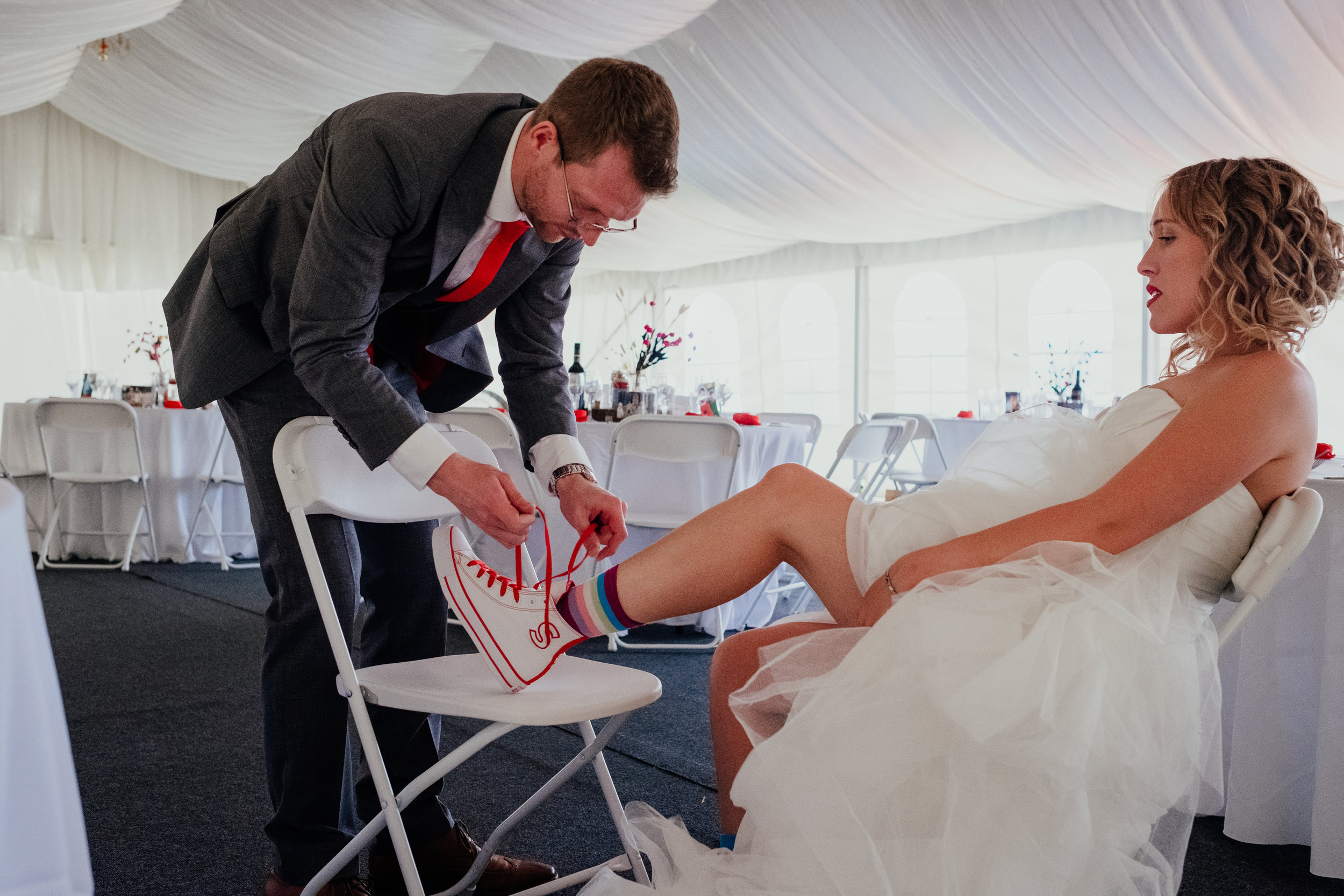 Groom helping bride put on wedding converse